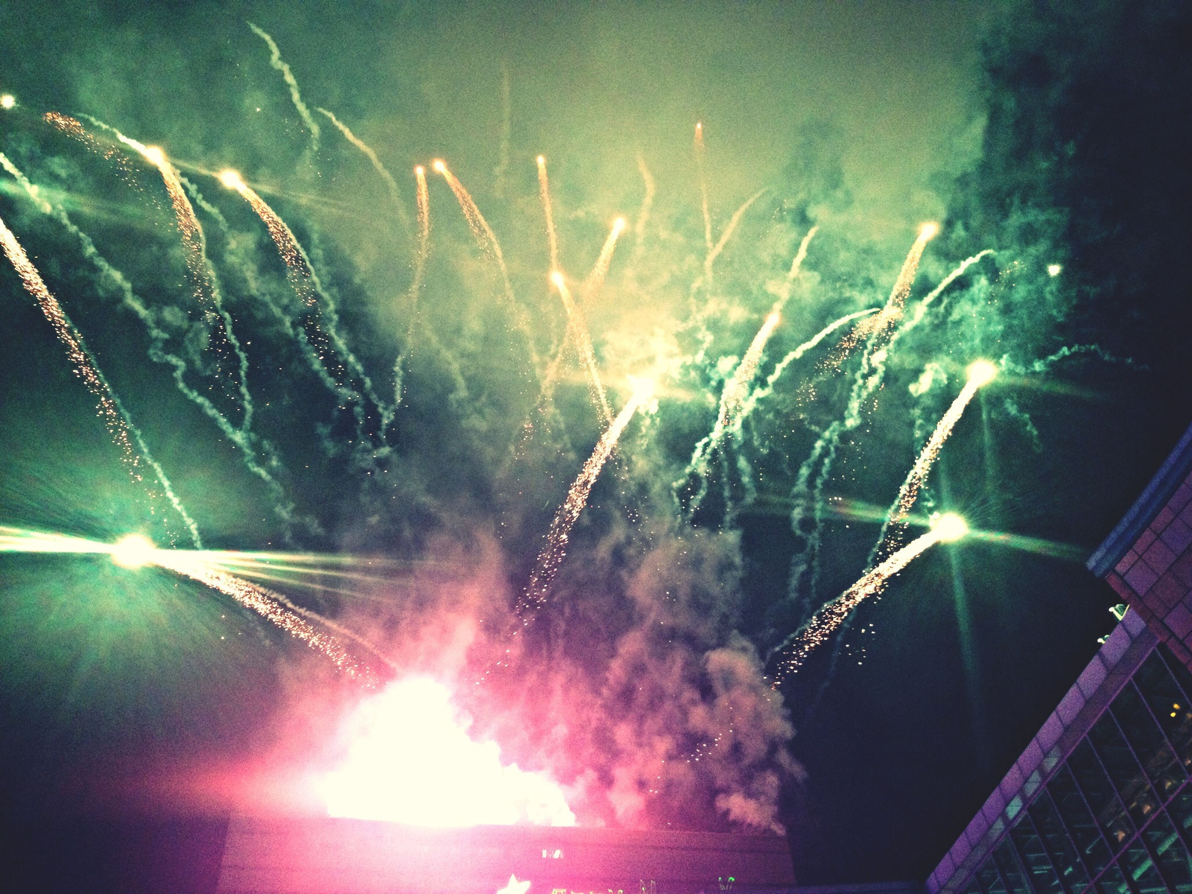 night, illuminated, glowing, long exposure, firework display, motion, exploding, sky, sparks, firework - man made object, low angle view, firework, arts culture and entertainment, celebration, thunderstorm, no people, outdoors, light, light - natural phenomenon, blurred motion