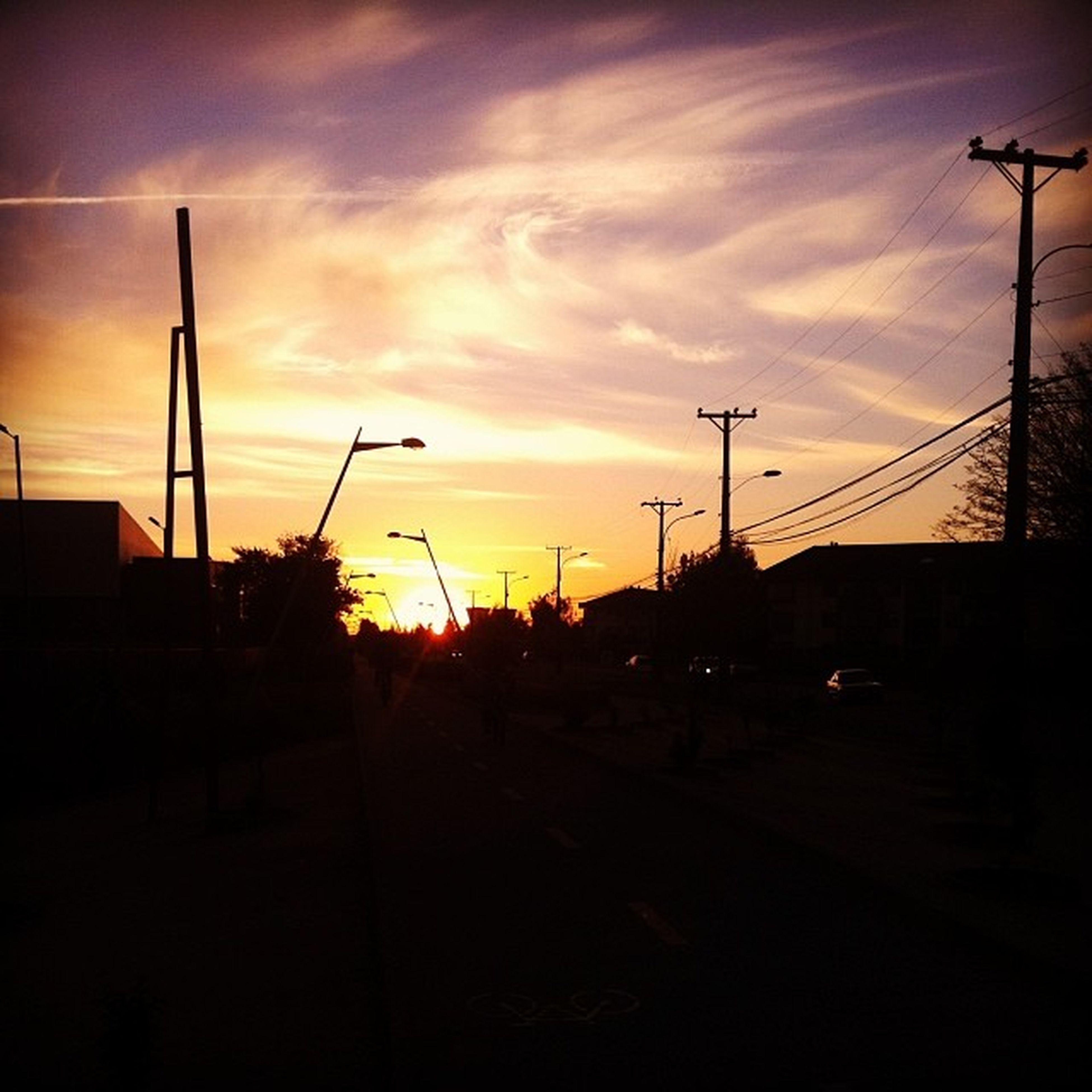 sunset, silhouette, orange color, sky, built structure, building exterior, architecture, street light, transportation, sun, electricity pylon, cloud - sky, car, sunlight, road, dark, power line, street, city, connection