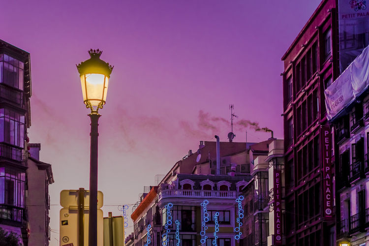 Evening view of smoke coming out of a chimney from a building in Calle Mayor, Madrid. City Life City Street Cityscape Roof Rooftop Smoke Traveling Architecture Building Exterior Built Structure City City Lights Destination Illuminated Lighting Equipment Low Angle View Night No People Outdoors Purple Sky Street Light Sunset