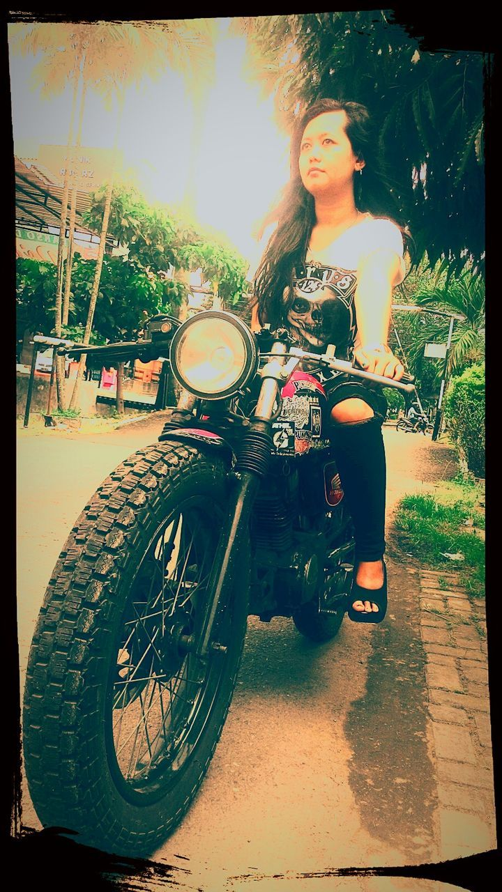 motorcycle, real people, transportation, young adult, full length, land vehicle, one person, front view, looking at camera, young women, portrait, mode of transport, day, lifestyles, leisure activity, standing, outdoors, beautiful woman, people