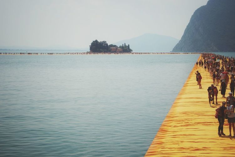 Walking on the Floating piers   People Walking Sunshine Feel The Journey Edge Of Imagination The Floating Piers Nature Lake Still Life The Essence Of Summer Original Experiences Getting Inspired Christo And The Floating Piers Fine Art Close-up Tailored To You Point Of View Golden Moments  Showcase July 43 Golden Moments Umbrellas Lago D'Iseo EyeEm Italy  