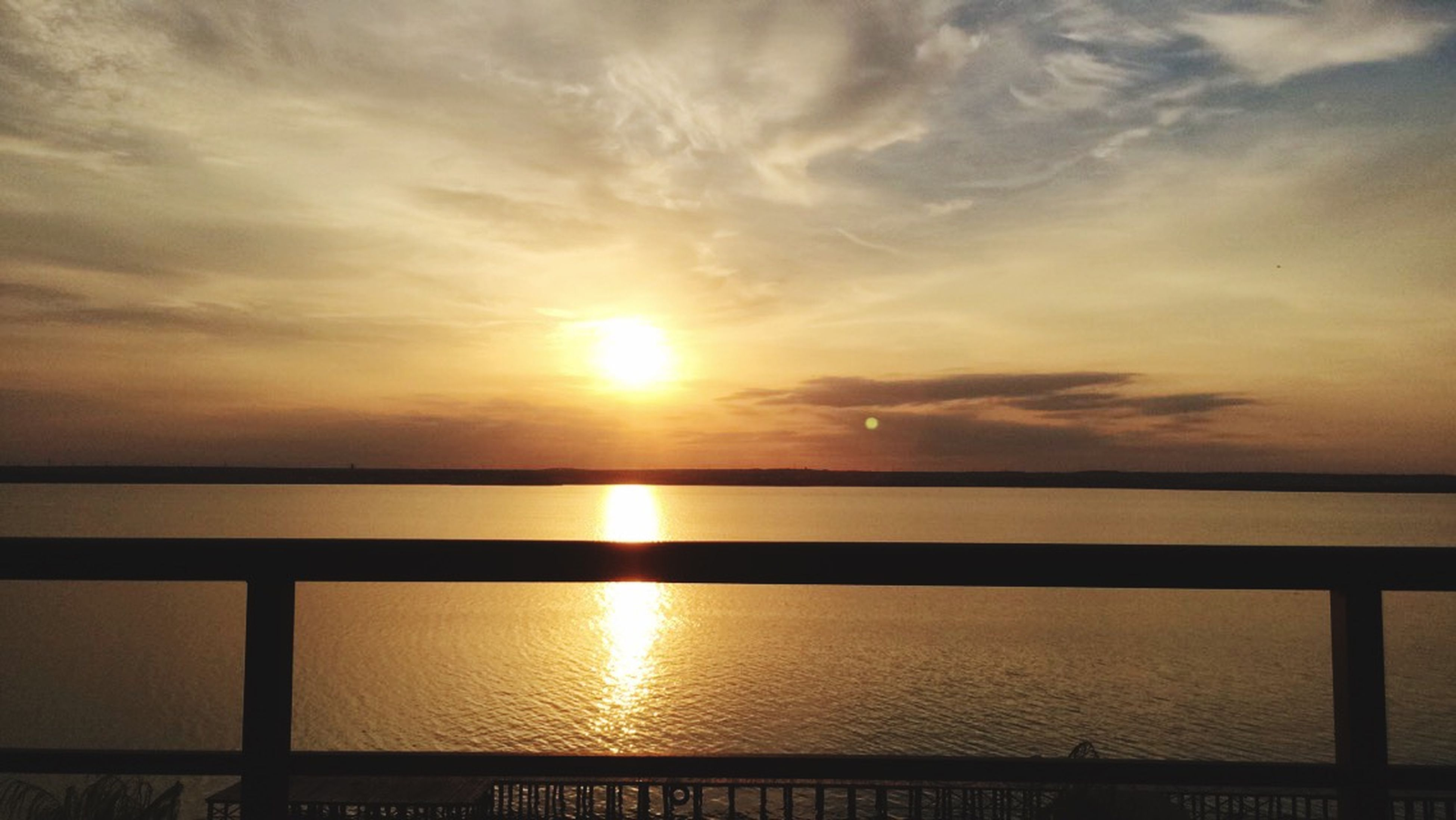 sunset, water, sun, sky, scenics, sea, tranquil scene, beauty in nature, reflection, orange color, tranquility, cloud - sky, idyllic, horizon over water, nature, silhouette, sunlight, cloud, railing, outdoors