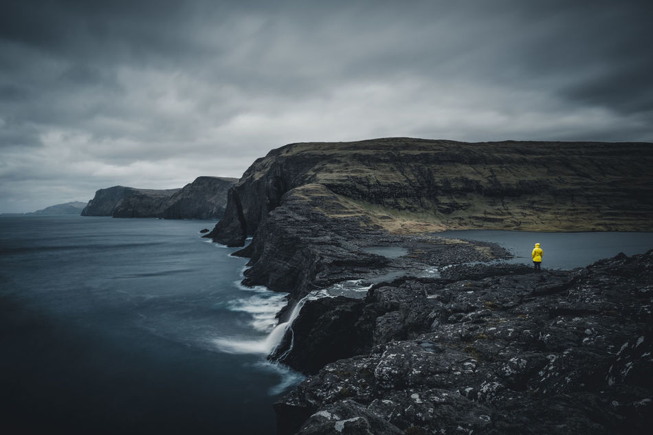 This waterfall (called Bøsdalafossur) flows from the largest lake on the Faroe Islands Sørvágsvatn into the North Atlantic Ocean. It is a surreal place on the edge between the calm lake and the rough sea. Just standing there in the cold fresh wind, exposed to the white sea spray and listening to the sound of the waves - is there anything better? Location: Bøsdalafossur, Faroe Islands Equipment: Fujifilm X-T2 + XF14 F2.8 R www.instagram.com/nils_leithold Adventure Beauty In Nature Bøsdalafossur Cliff Cloud - Sky Day Faroe Islands Jacket Lonely Moody Mountain Nature One Person Outdoors People Rock - Object Rock Formation Scenics Sea Sky Tranquil Scene Tranquility Water Waterfall Yellow