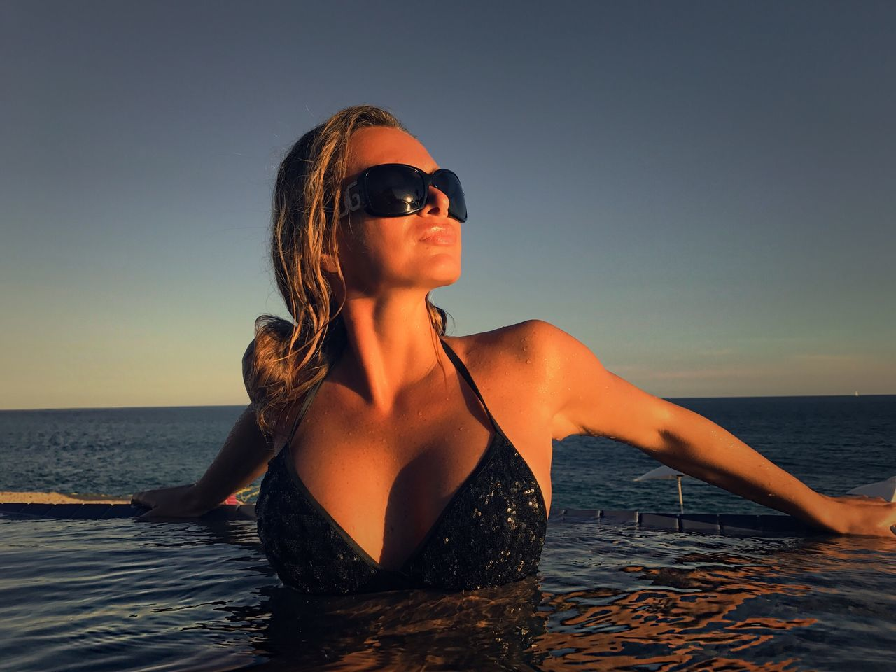 Infinity Pool Swimming Pool Vacations Evening Sunset Ocean Woman Leisure Activity Lifestyles Sea Real People Water Horizon Over Water One Person Clear Sky Sunglasses Outdoors Beach