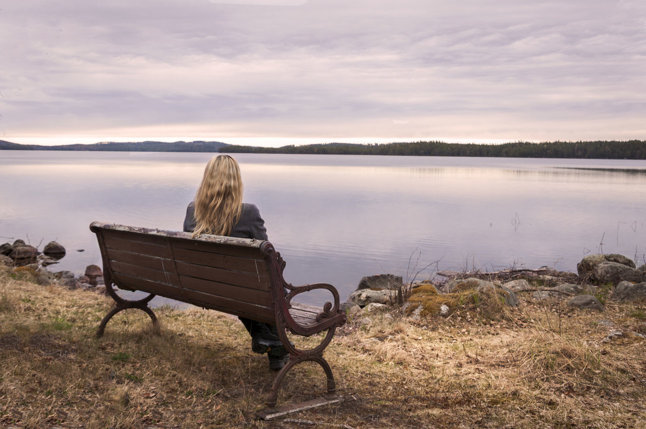 rear view, one person, nature, lake, leisure activity, sky, tranquility, tranquil scene, blond hair, beauty in nature, scenics, women, relaxation, full length, water, sitting, outdoors, day, real people, young women, young adult, adult, people