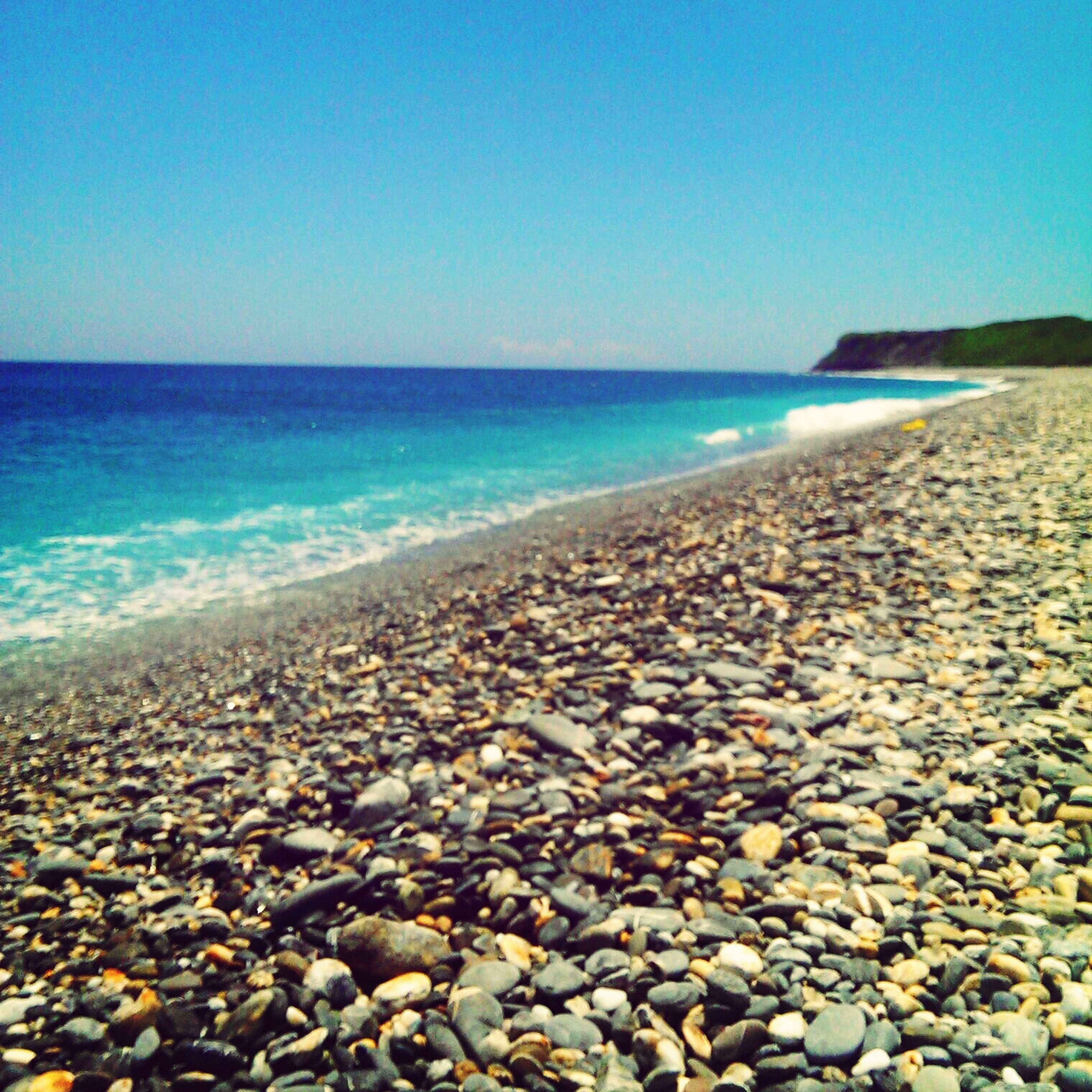 sea, horizon over water, water, beach, clear sky, scenics, shore, tranquil scene, tranquility, beauty in nature, blue, pebble, copy space, stone - object, nature, rock - object, idyllic, sky, coastline, seascape