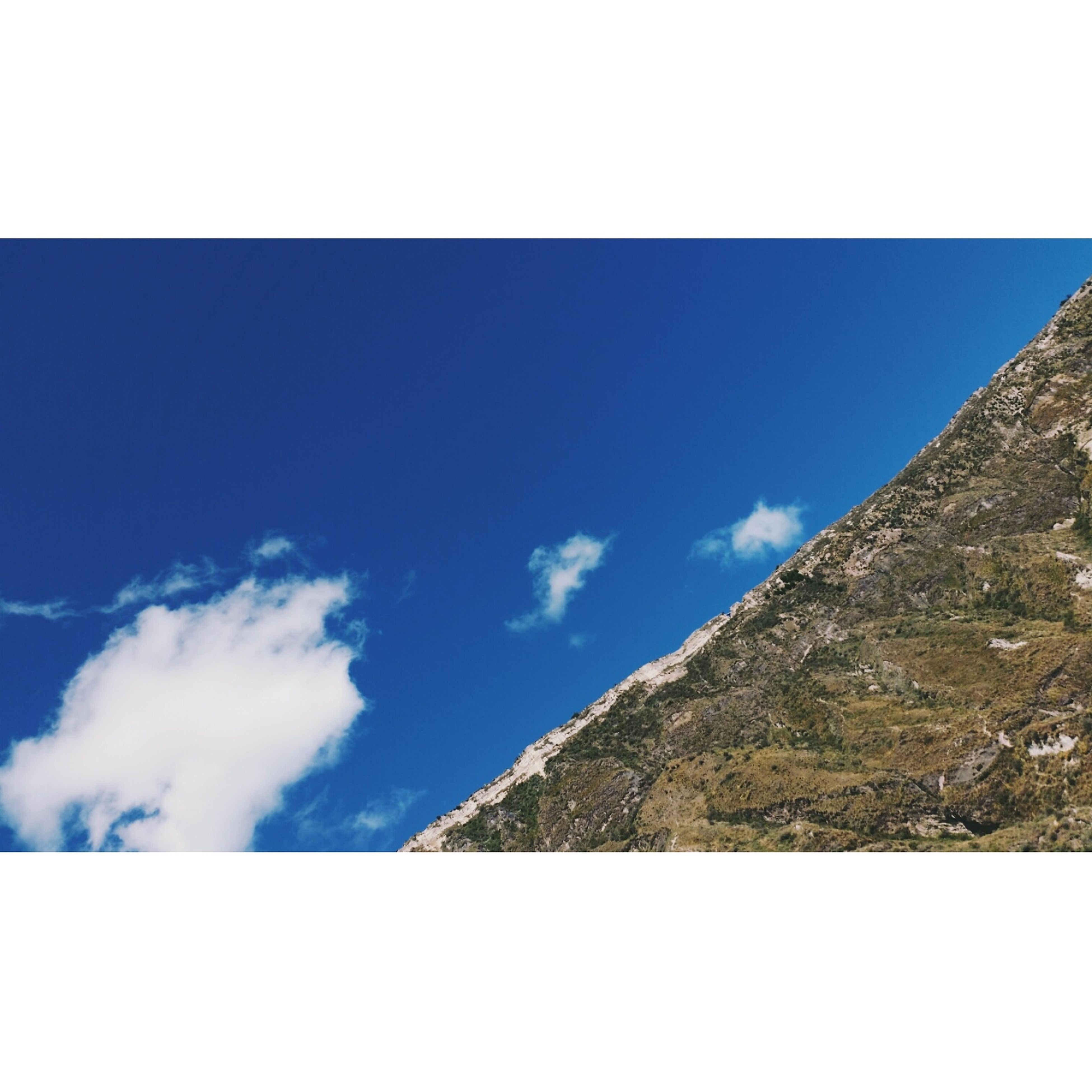 blue, sky, auto post production filter, low angle view, tranquil scene, transfer print, scenics, tranquility, mountain, beauty in nature, cloud, nature, day, outdoors, mountain range, cloud - sky, no people, non-urban scene, majestic, remote, solitude, rocky