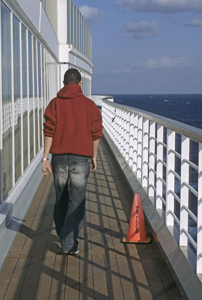 walking on cruise ship deck and a wet floor cone Cruise Liner Cruise Ship Exterior Man Passenger Railing Rear View Sign Boat Casual Clothing Cone Deck Horizon Over Water Male Navigation One Person Outdoors People Real People Safety Sea Ship Vacation Walking Wet Floor