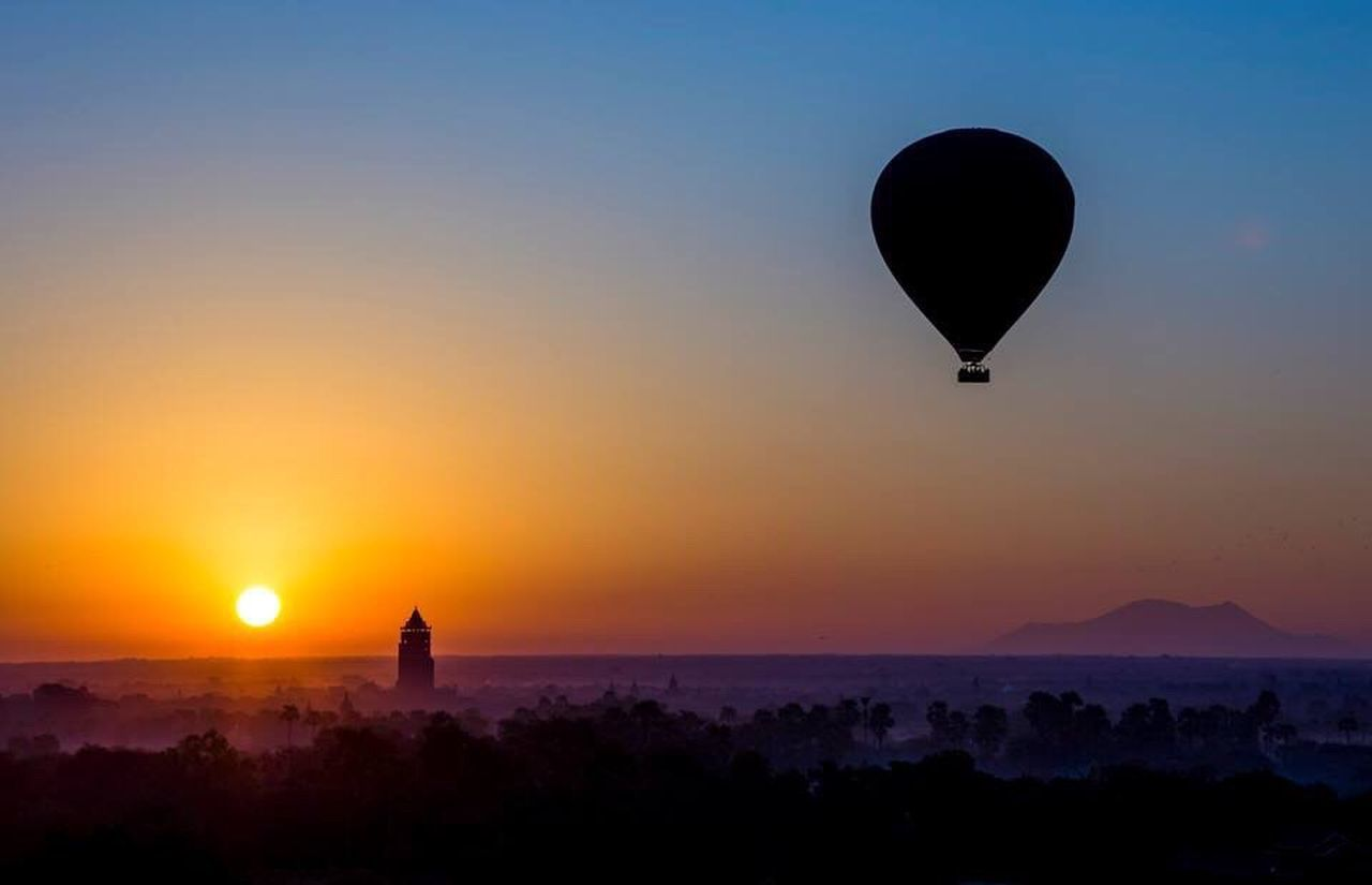 sunset, silhouette, sky, beauty in nature, hot air balloon, nature, sun, building exterior, built structure, no people, outdoors, scenics, architecture, water, sea, clear sky, tree, day