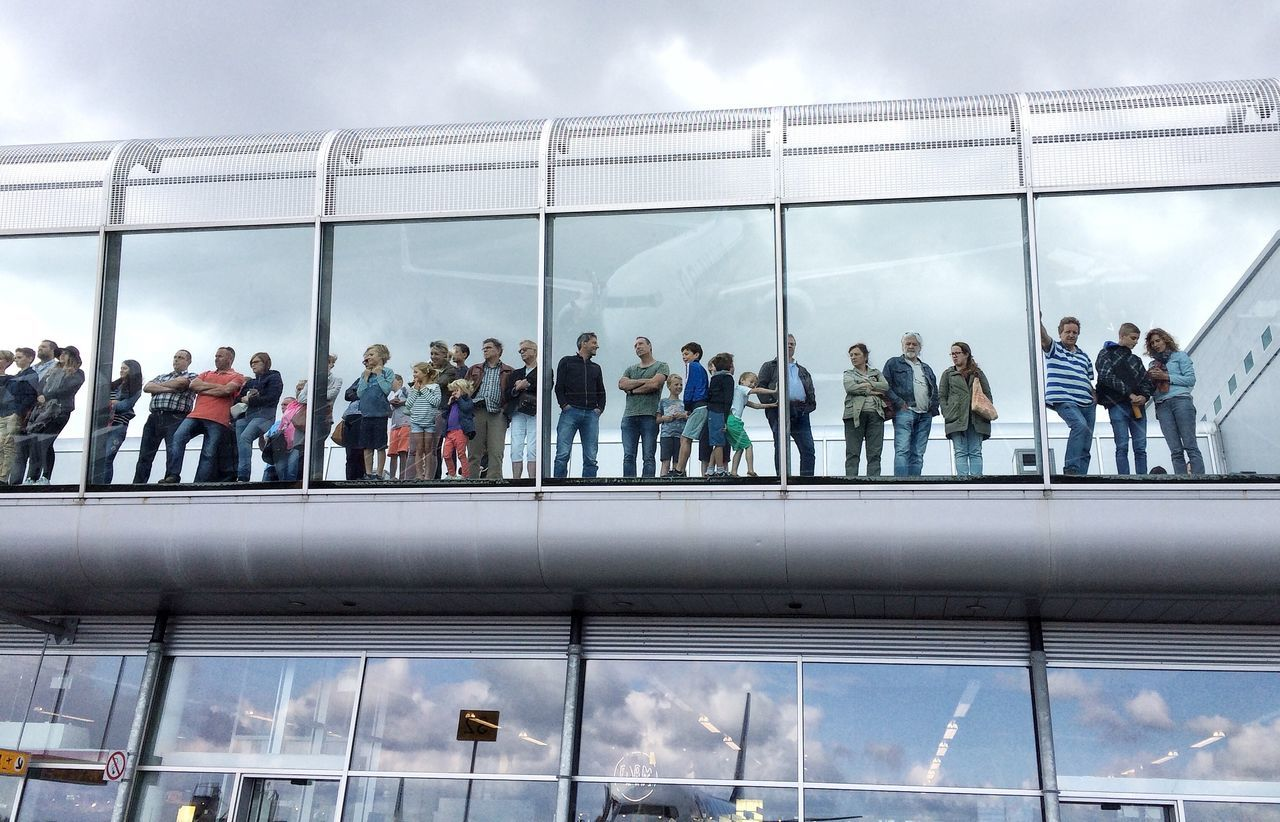 architecture, built structure, men, large group of people, sky, person, glass - material, lifestyles, low angle view, indoors, cloud - sky, modern, leisure activity, day, building exterior, railing, walking, travel, reflection