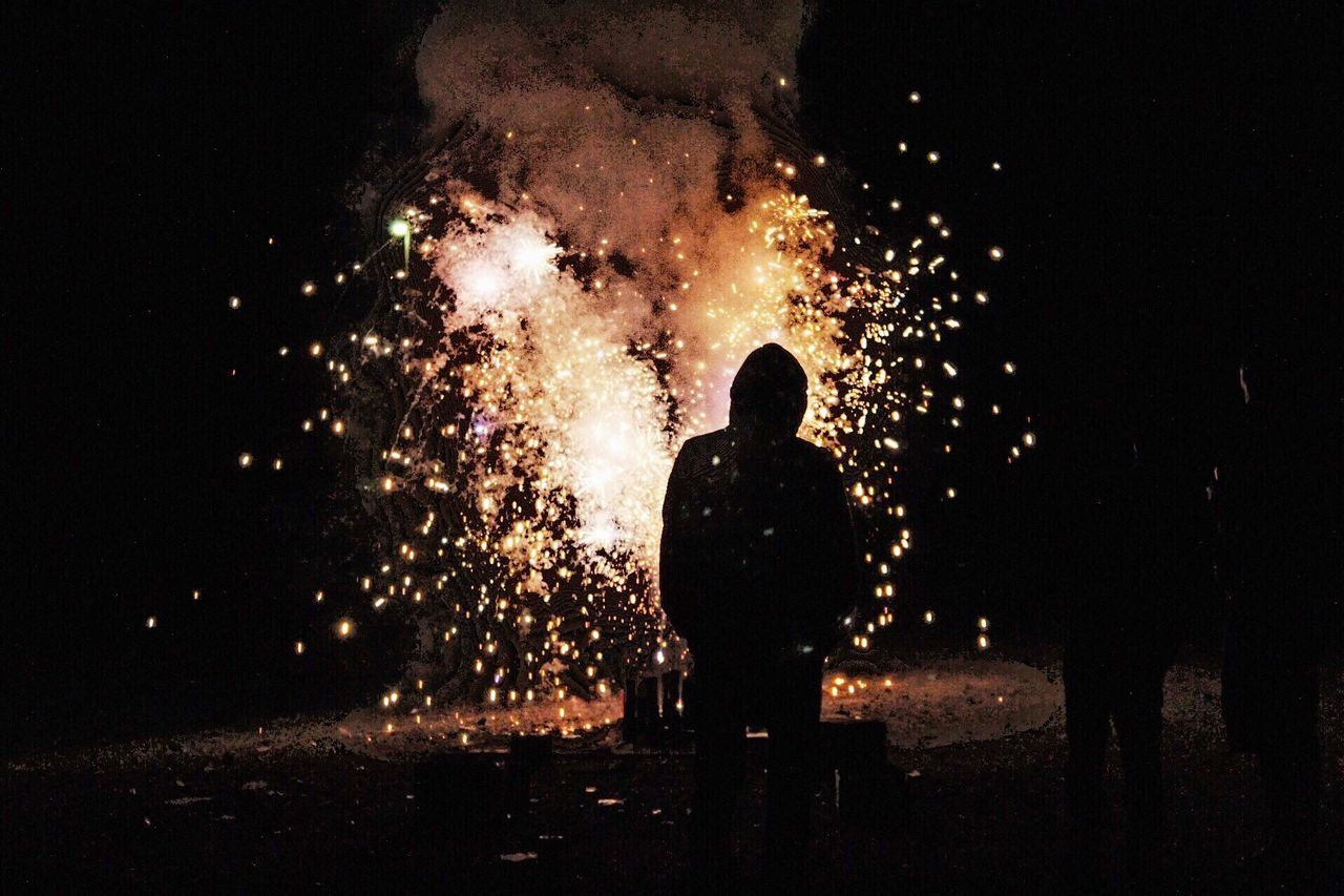 night, exploding, firework display, firework - man made object, real people, sparks, glowing, standing, silhouette, long exposure, one person, burning, motion, rear view, celebration, arts culture and entertainment, firework, men, outdoors, illuminated, lifestyles, sky, people