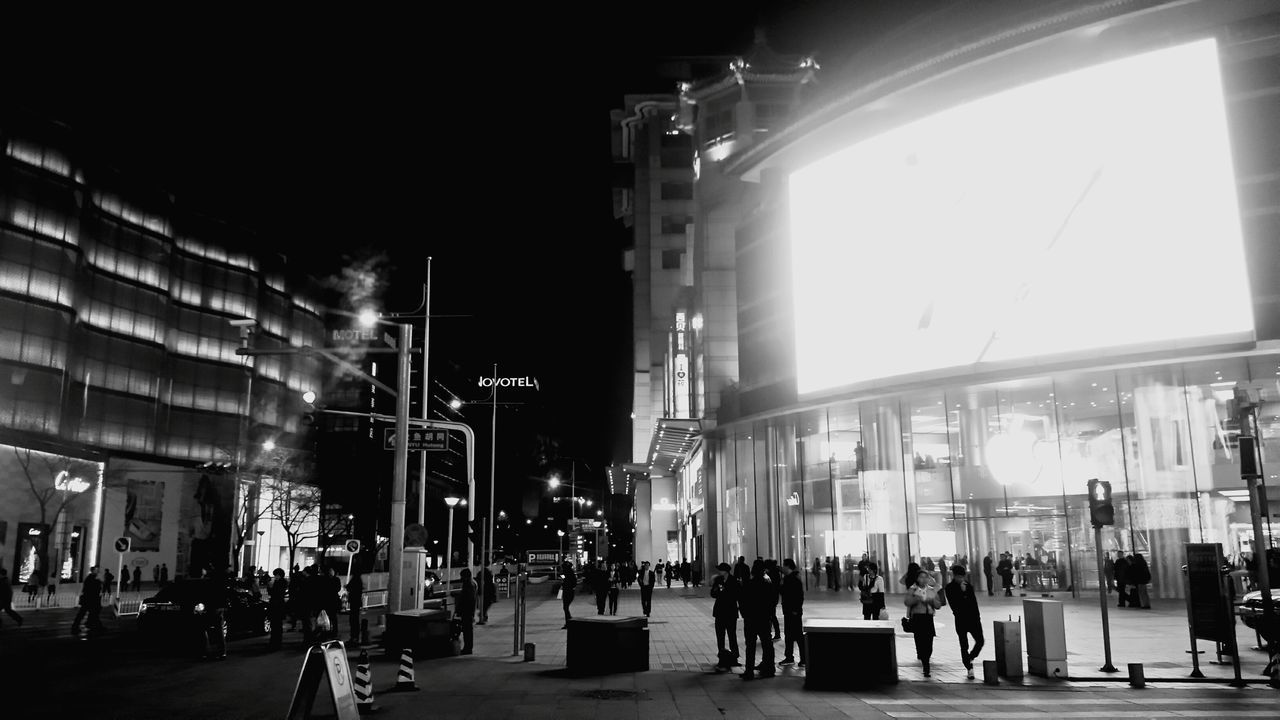 building exterior, built structure, architecture, city, real people, city life, night, illuminated, walking, large group of people, travel destinations, outdoors, sky, women, men, people