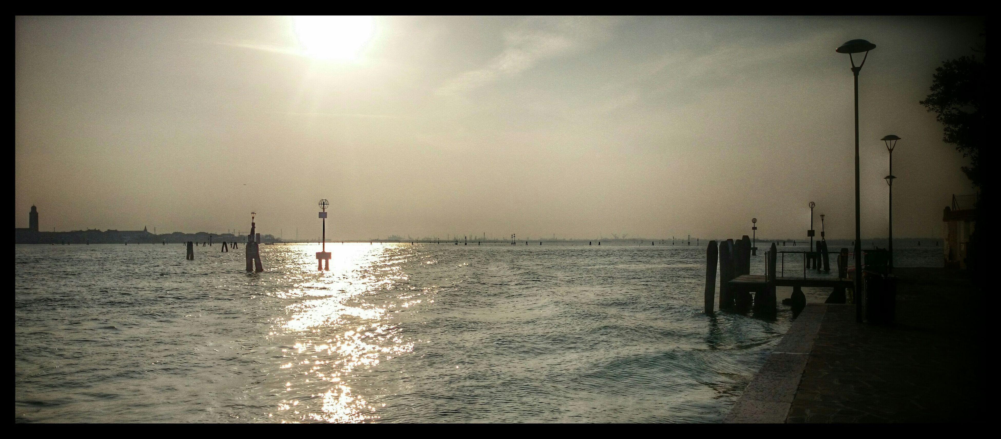 water, sea, horizon over water, transfer print, tranquility, sky, tranquil scene, scenics, beauty in nature, pier, beach, sun, nature, auto post production filter, sunset, shore, idyllic, reflection, street light, sunlight