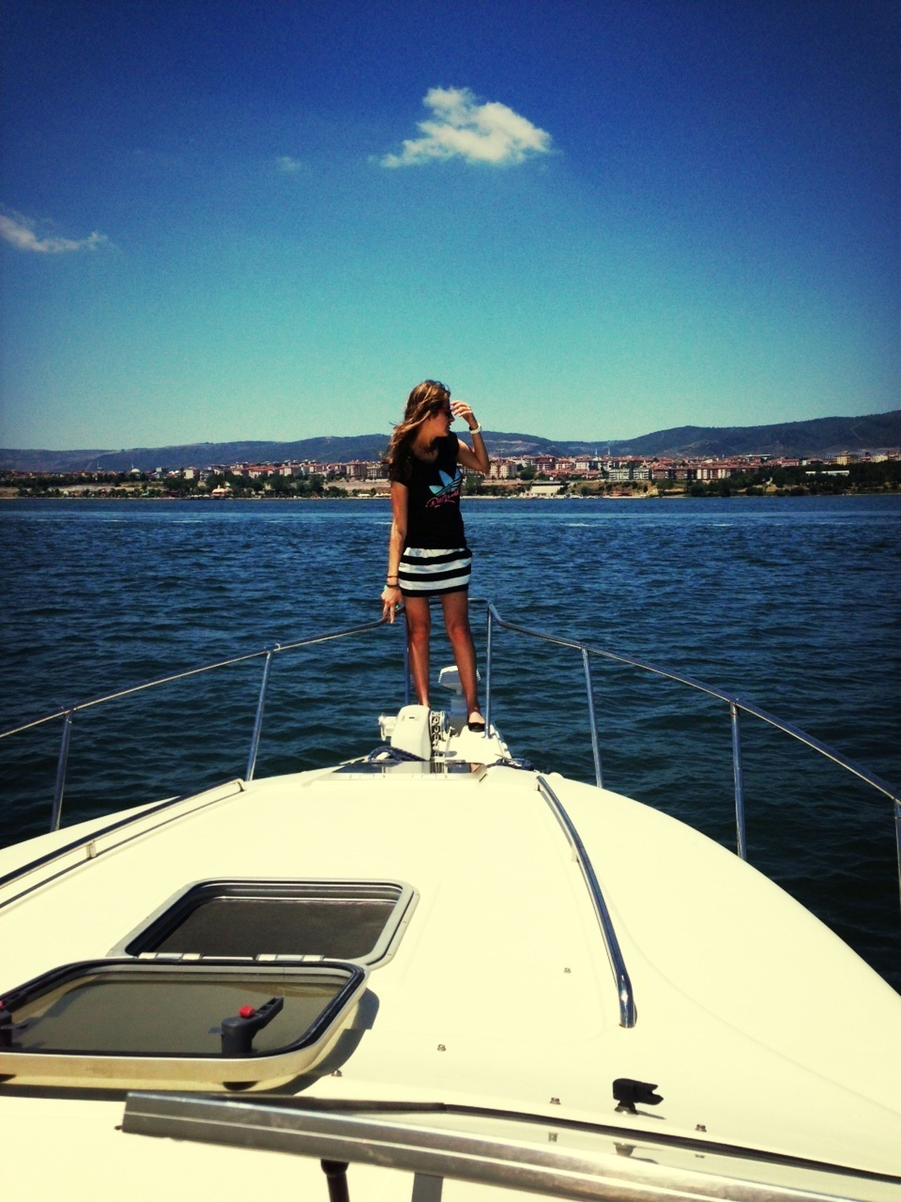 water, blue, lifestyles, sea, full length, transportation, leisure activity, nautical vessel, standing, casual clothing, rear view, sky, railing, young adult, mode of transport, person, day, boat