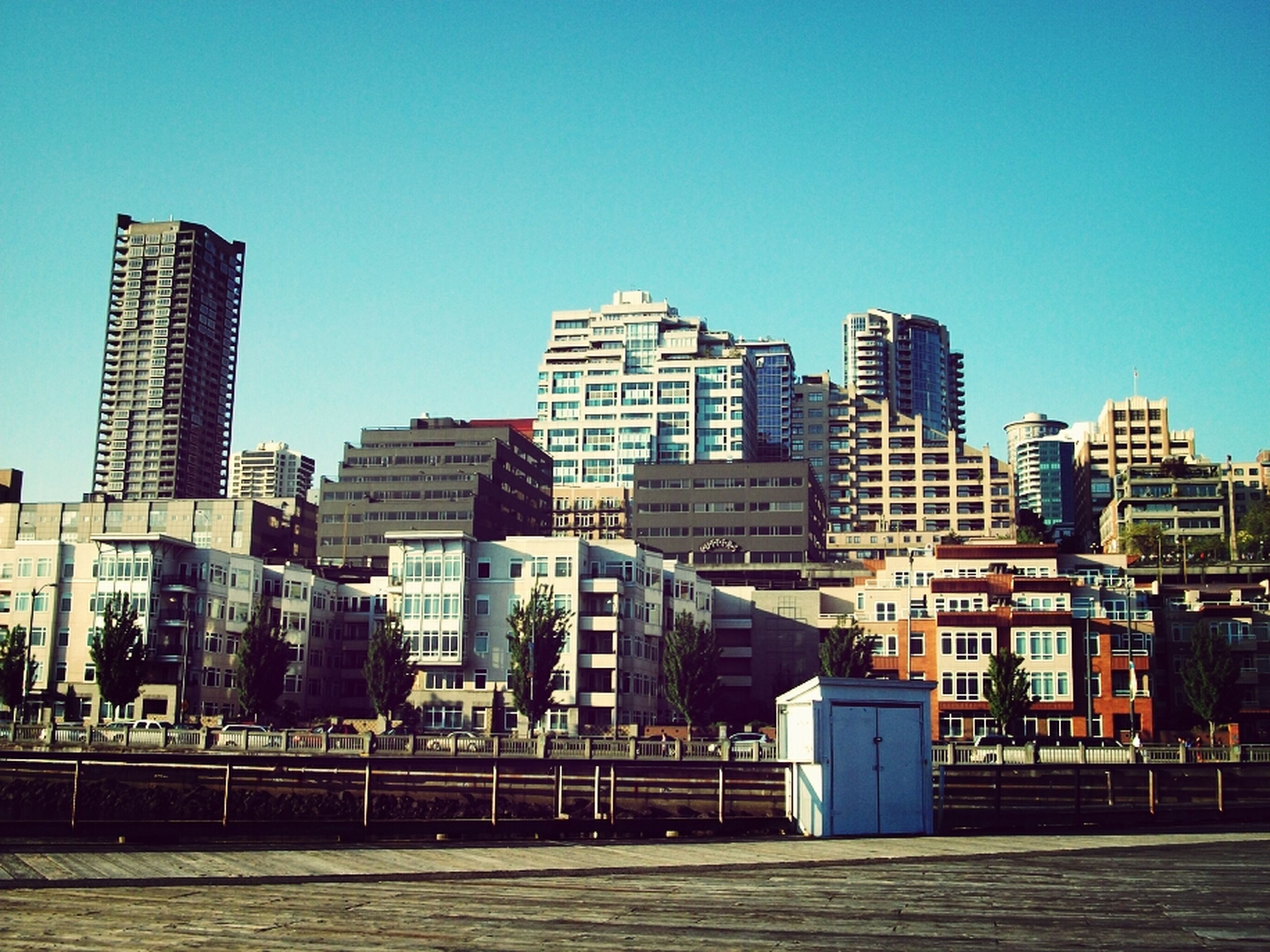 building exterior, architecture, built structure, clear sky, city, blue, copy space, cityscape, residential structure, residential building, building, residential district, outdoors, sunlight, sky, city life, day, no people, skyscraper, house