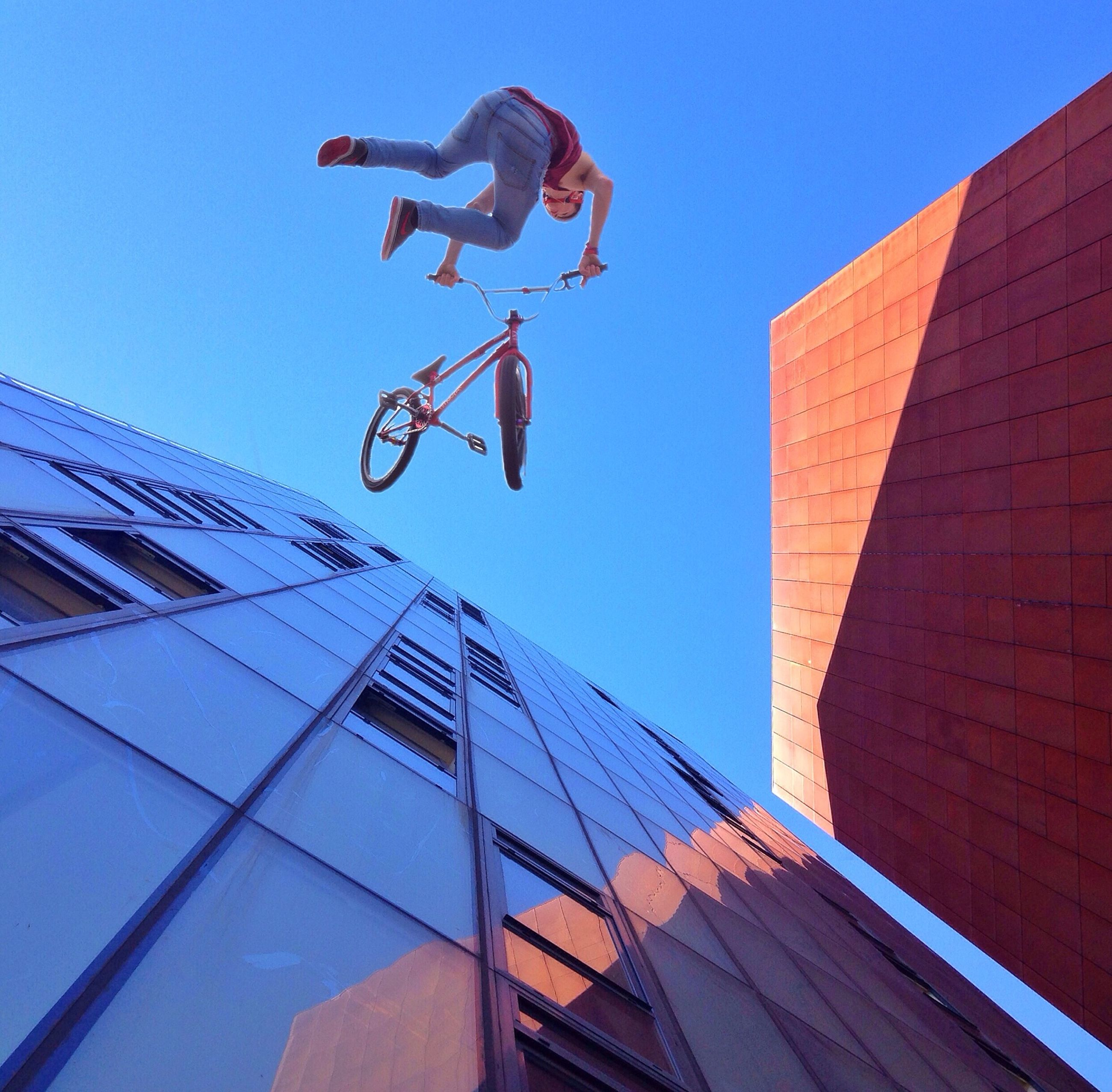 low angle view, architecture, built structure, building exterior, clear sky, blue, city, day, mid-air, outdoors, building, sunlight, modern, leisure activity, sky, men, flying, lifestyles