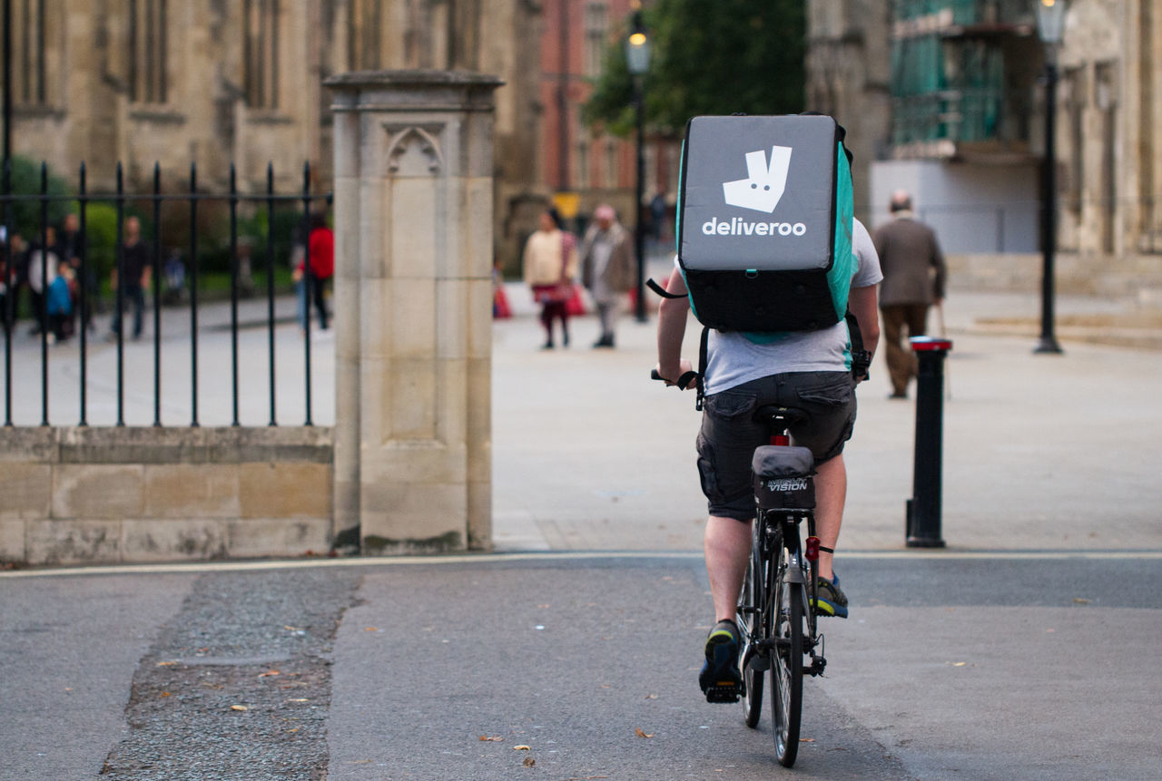 A cyclist from the increasingly popular take away food delivery company Deliveroo speeding through city streets with a hot food delivery from take aways and restaurants to people's homes. Bicycle Bicycles Bike Biker City Company Cyclist Deliver Delivering Deliveroo Delivery Delivery Service Fast Food Food Delivery Hot Food Local Pizza Pizza Delivery Man Quick Service Speed Speeding Street Take Away Food