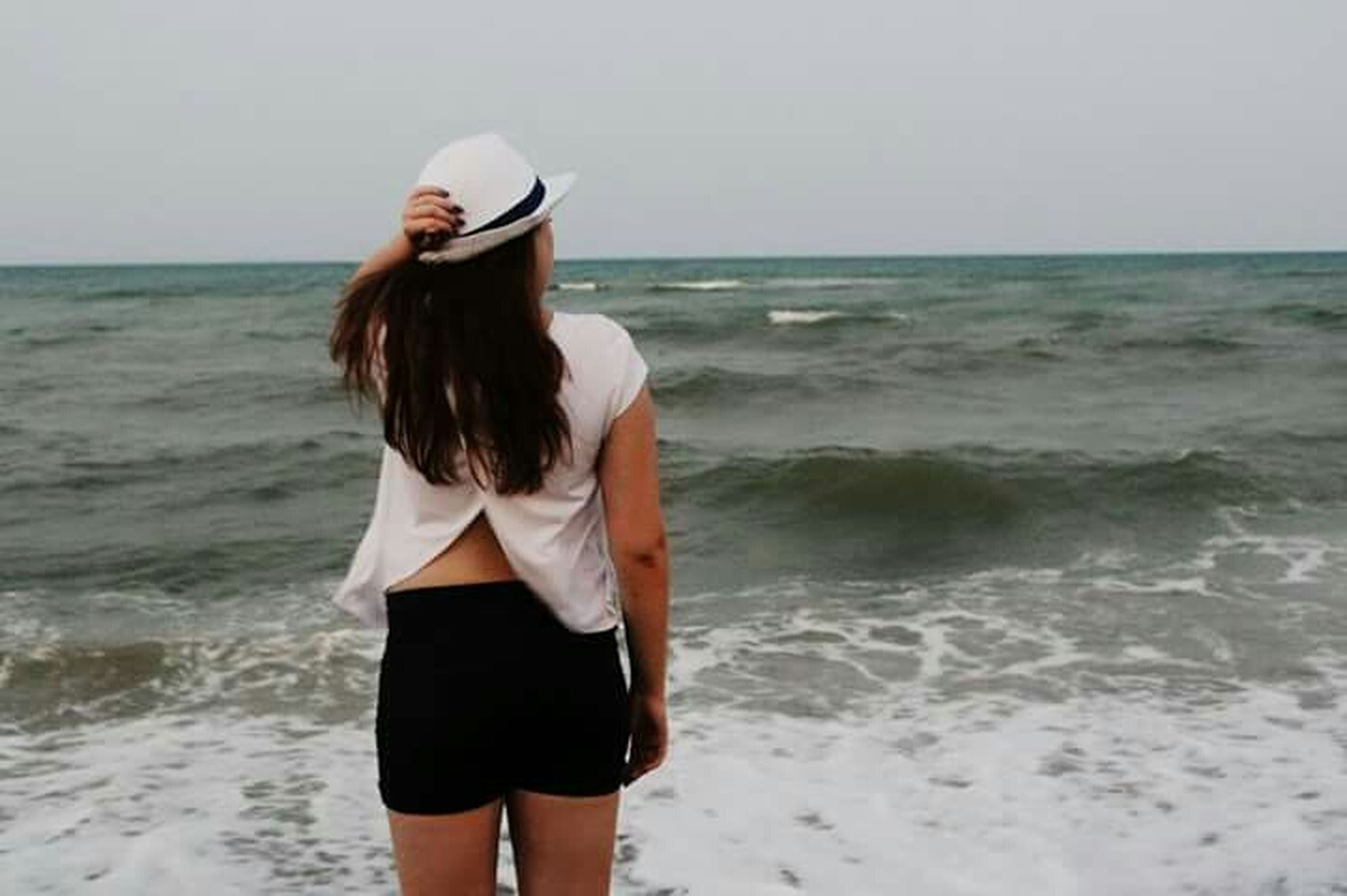 sea, water, horizon over water, beach, young adult, standing, lifestyles, young women, long hair, leisure activity, shore, three quarter length, rear view, person, casual clothing, vacations