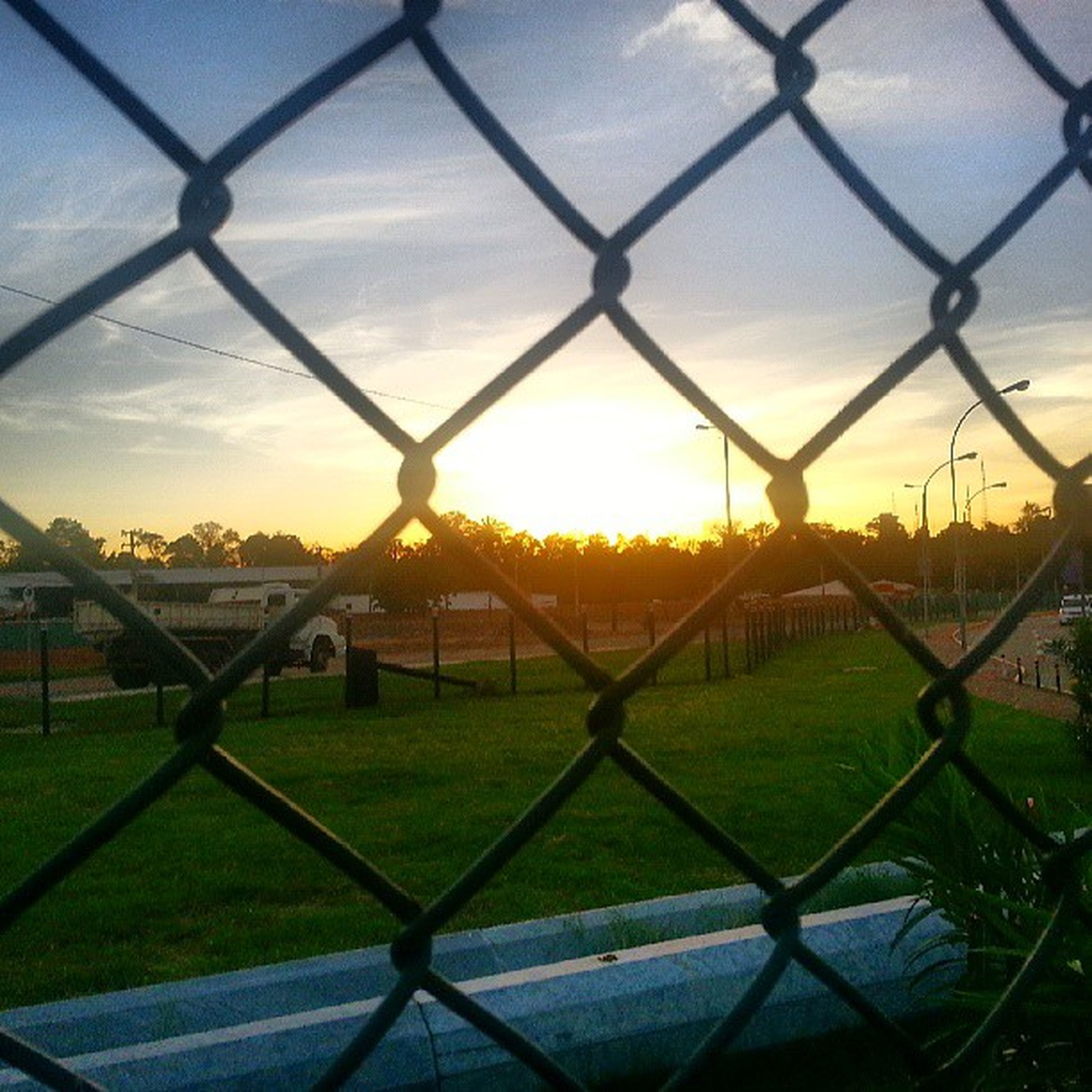 sunset, fence, chainlink fence, orange color, protection, safety, sky, field, sun, security, landscape, grass, metal, beauty in nature, tranquility, scenics, nature, tranquil scene, sunlight, no people