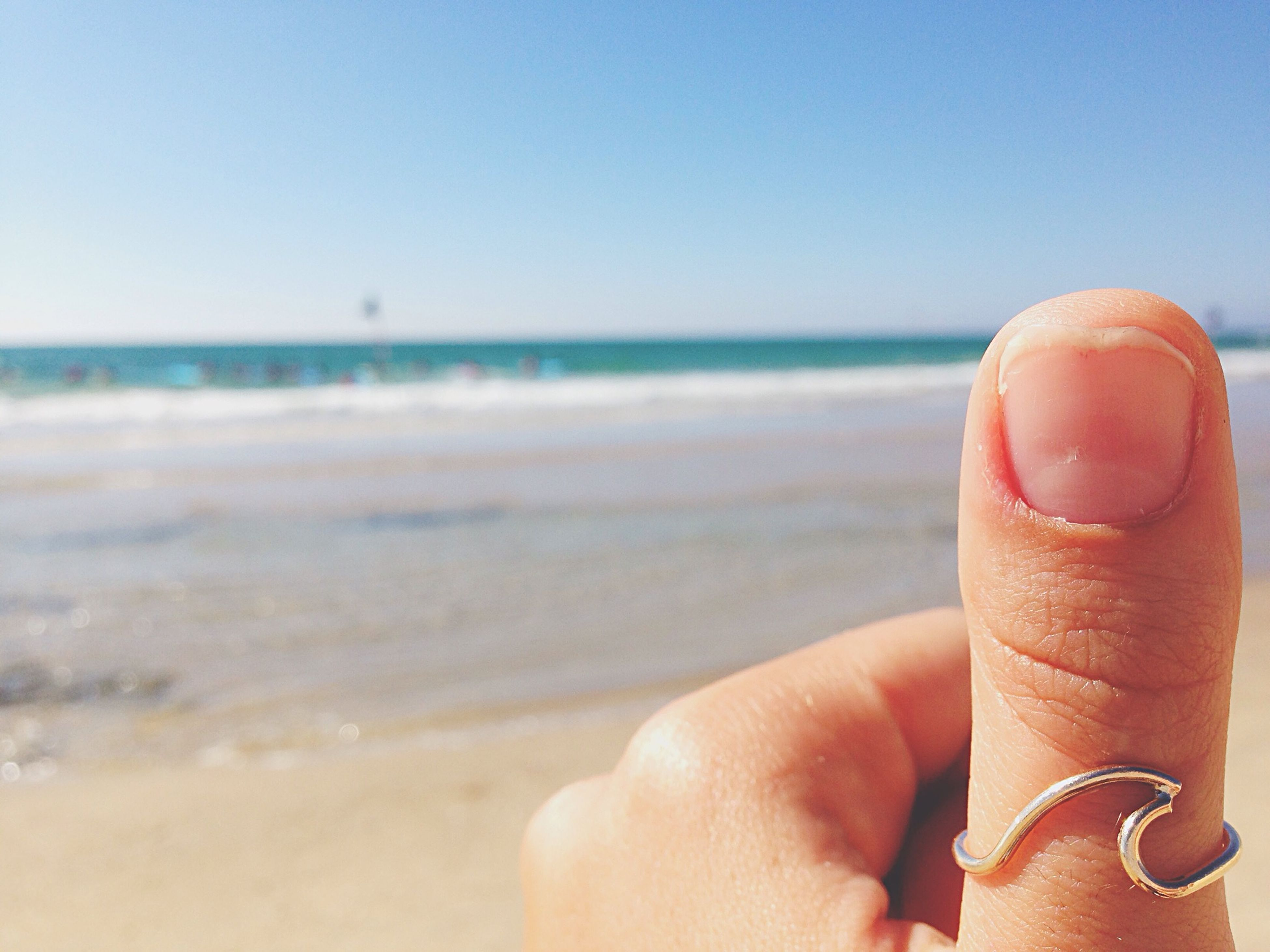 sea, horizon over water, beach, person, water, part of, cropped, clear sky, holding, personal perspective, lifestyles, leisure activity, copy space, sand, shore, close-up, focus on foreground