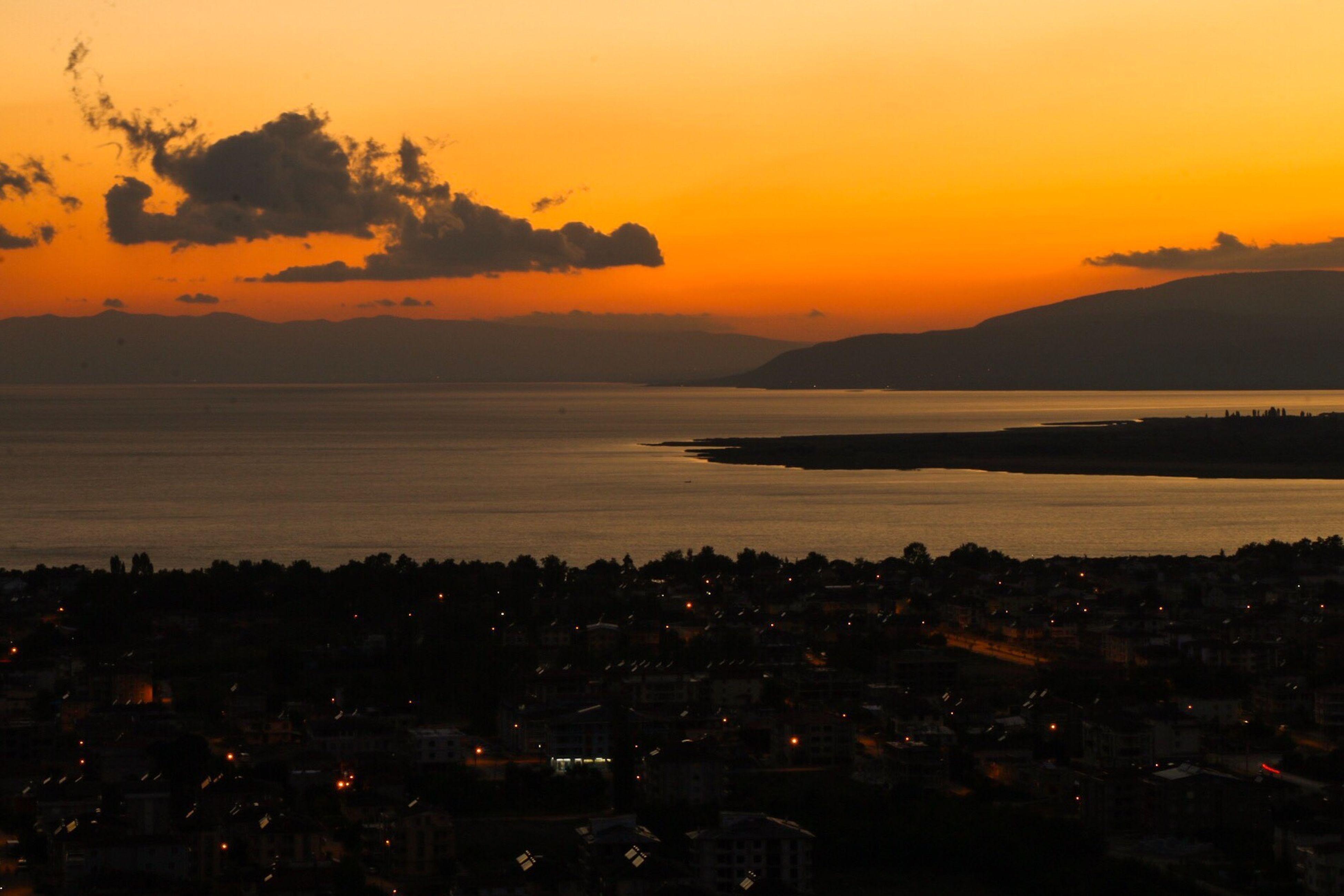 sunset, sea, water, orange color, scenics, mountain, beauty in nature, tranquil scene, sky, tranquility, idyllic, nature, cityscape, city, coastline, outdoors, illuminated, no people, mountain range, ocean, cloud - sky, majestic, remote