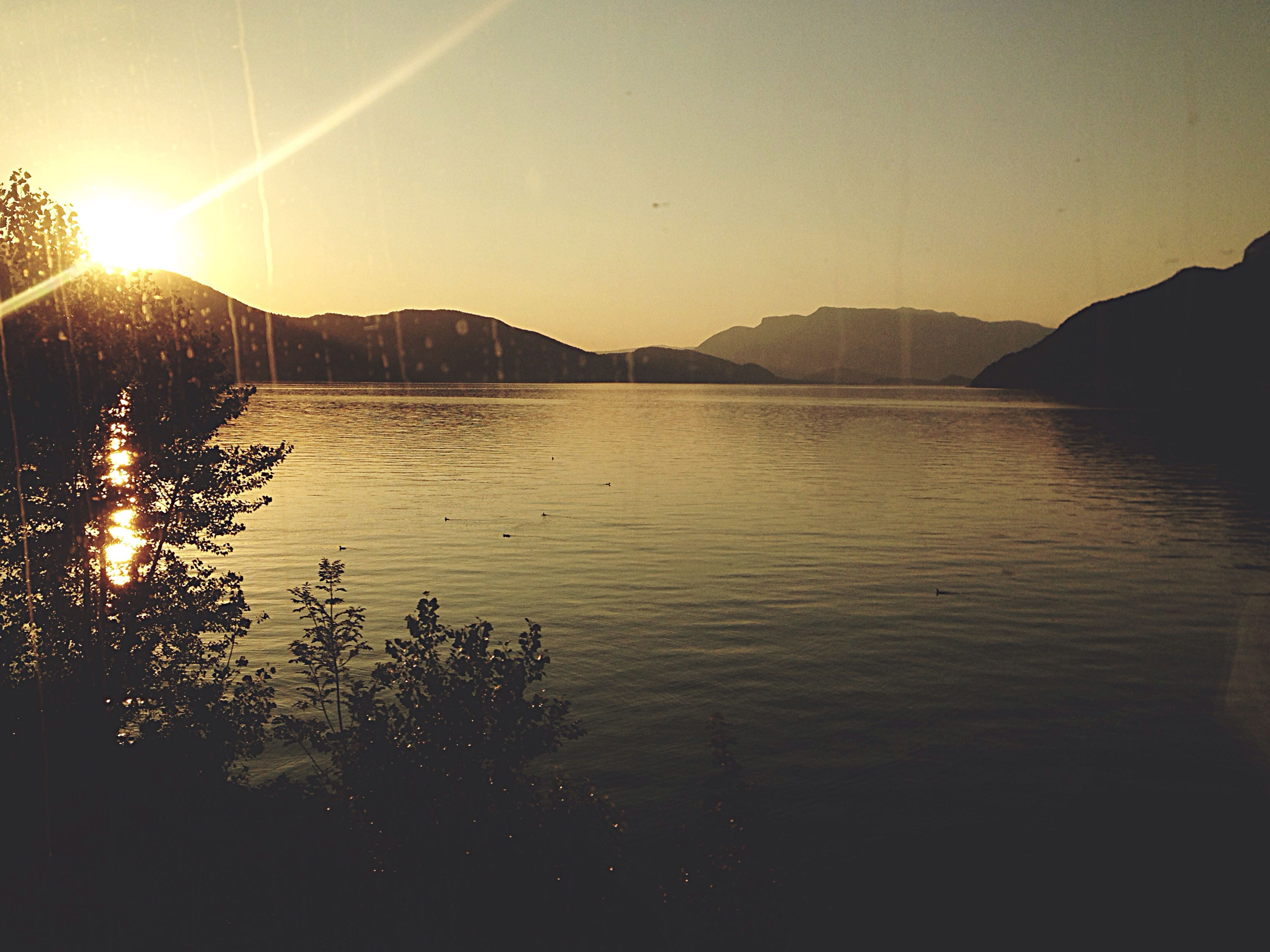 sun, water, mountain, sunbeam, tranquil scene, lens flare, scenics, tranquility, sunset, sunlight, beauty in nature, reflection, lake, river, nature, sky, silhouette, clear sky, idyllic, mountain range