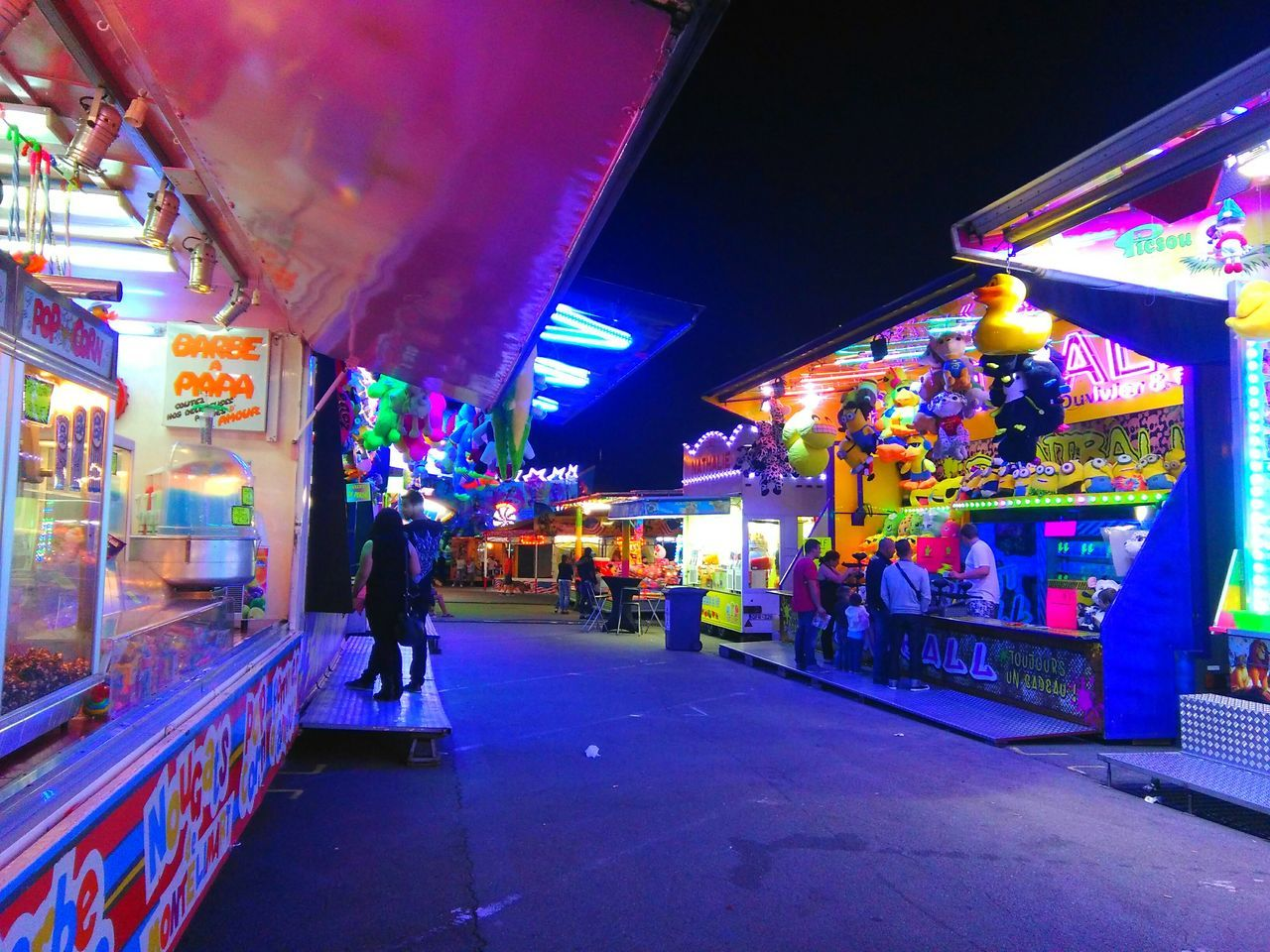 illuminated, night, real people, market, men, retail, multi colored, leisure activity, lifestyles, amusement park, walking, market stall, neon, consumerism, arts culture and entertainment, city, store, outdoors, architecture, built structure, women, awning, building exterior, carousel, people