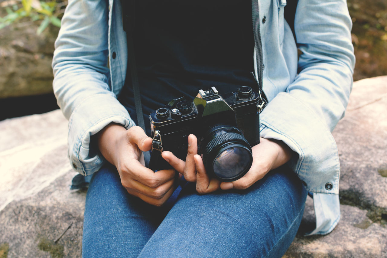 Midsection Of Woman Holding Camera