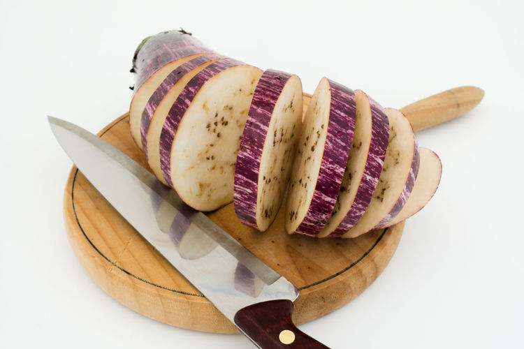 Cut eggplant with knife on wooden cutting board Eggplant Food And Drink Knife Nature Food Purple Eggplant SLICE Vegetarian Food Board Cooking Gesture Cutboard Cuttingboard Fresh Food Ingredient Isolated White Background Km0slowfood Nutrition And Dietetics Practicing Photography Preparation Of Food Raw Food Reflaction Stipes Studio Photography Top View Of Food Vegan Wood - Material