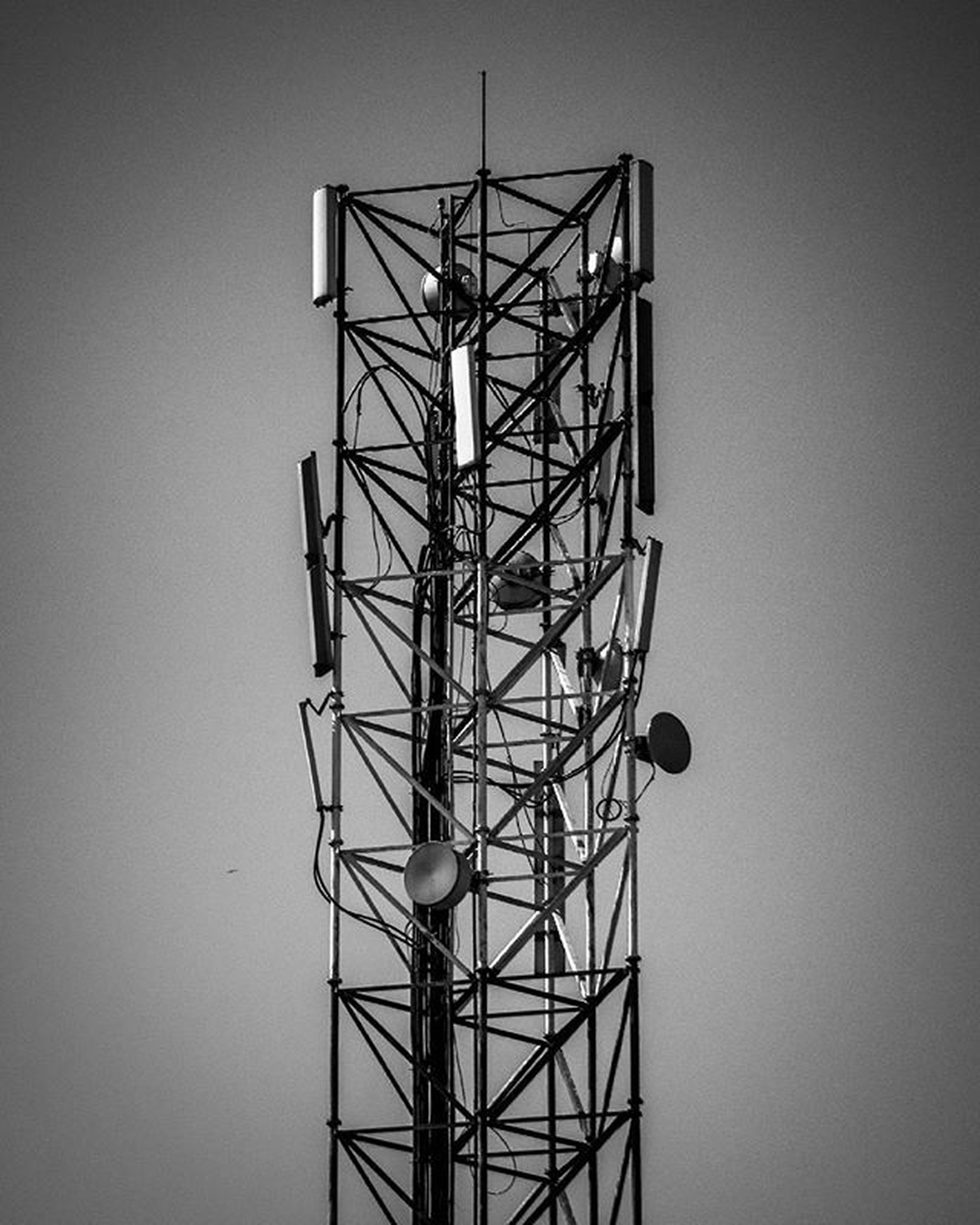 low angle view, clear sky, electricity, fuel and power generation, technology, built structure, copy space, sky, electricity pylon, silhouette, connection, metal, architecture, tall - high, lighting equipment, power supply, no people, outdoors, dusk, tower