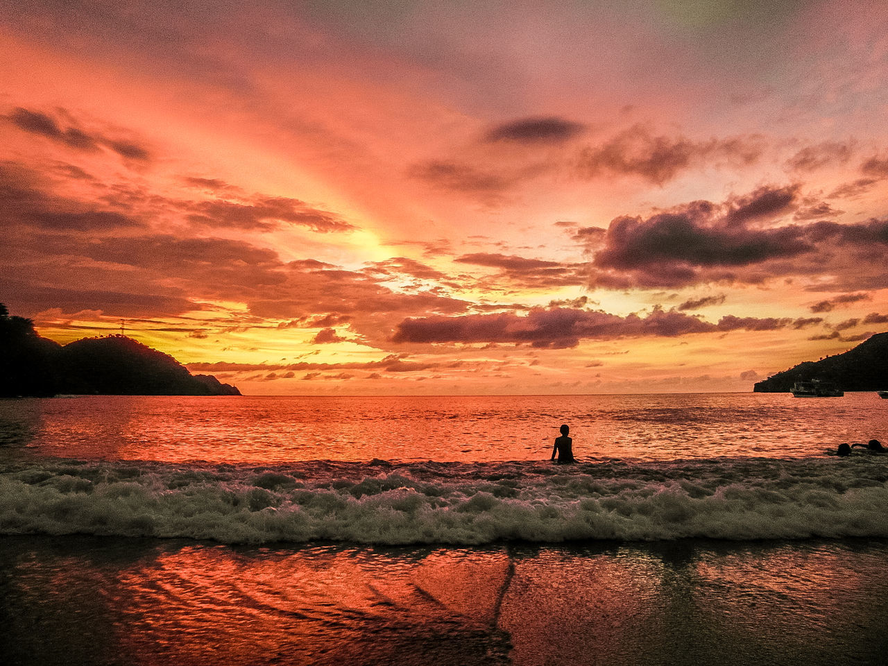 Young boy in the water during sunset at the beach Beach Beauty In Nature Boy Cloud - Sky Colombia Horizon Over Water Nature Sand Scenics Sea Silhouette Sky Sunset Tranquility Travel Travel Destinations Vacations Water