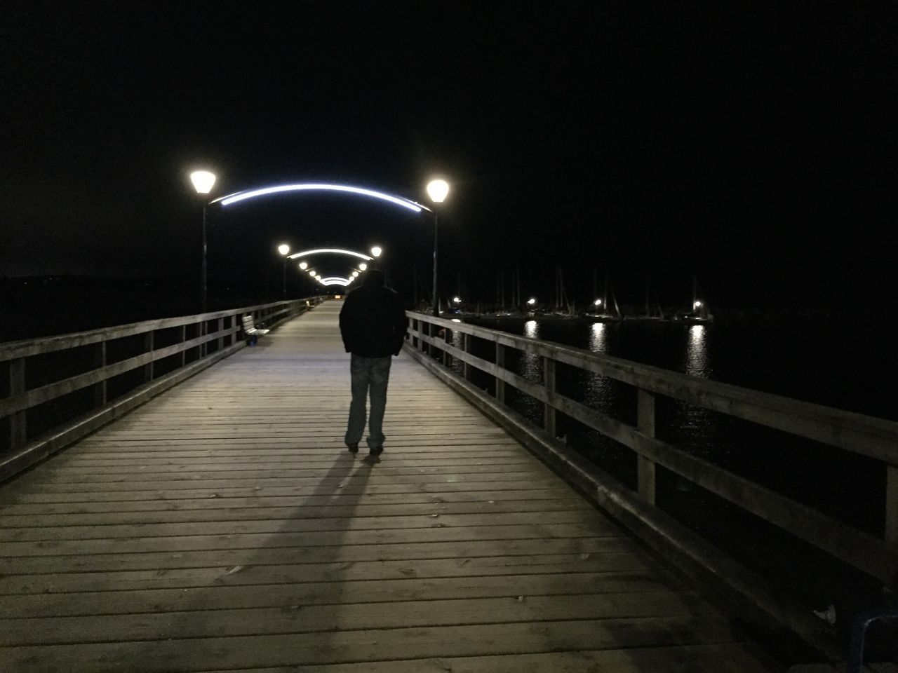 White rock pier at night Night Illuminated Bridge - Man Made Structure Street Light Full Length Lighting Equipment Railing The Way Forward One Person Walking Real People Transportation Rear View Men Outdoors People