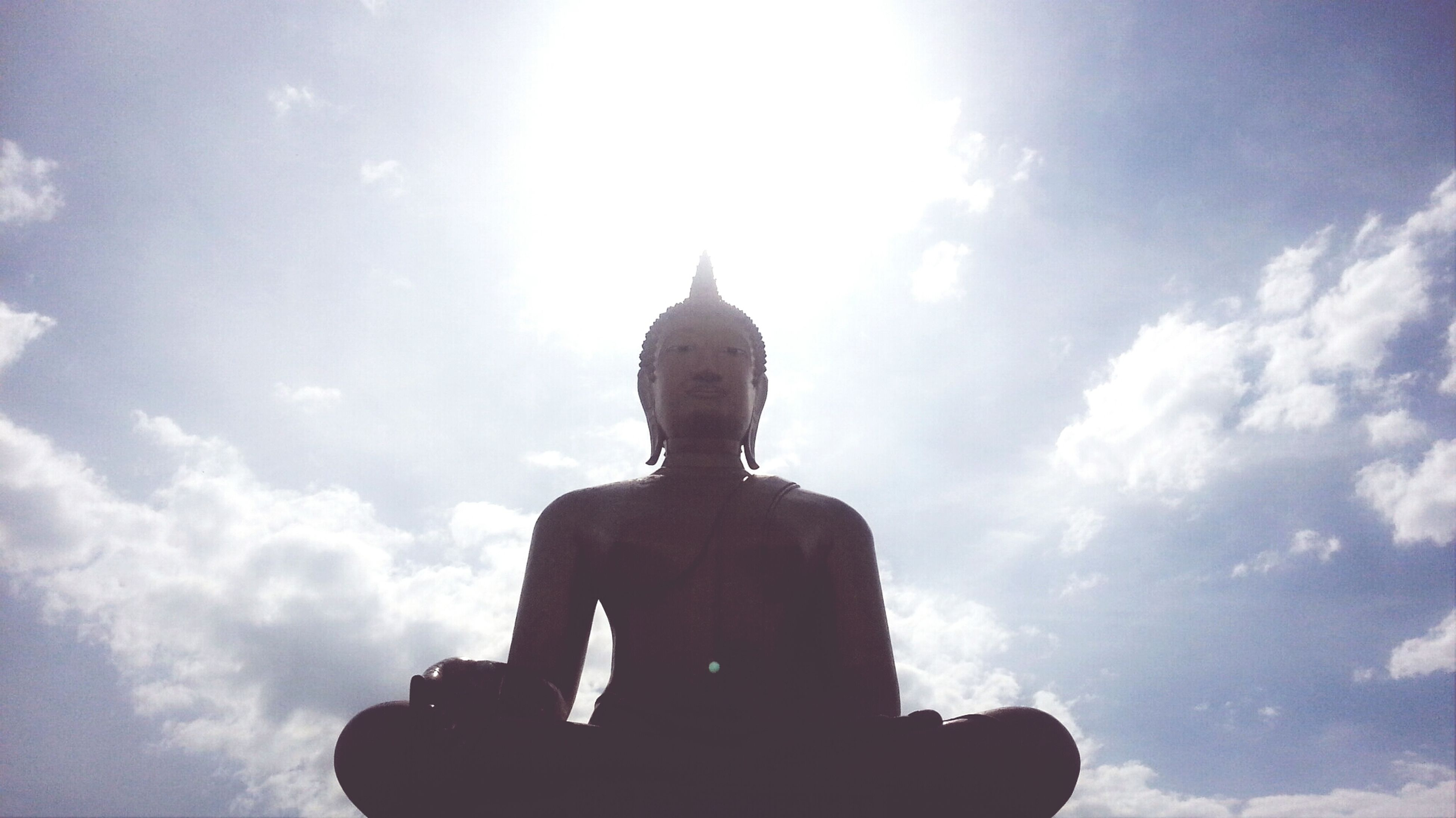 human representation, statue, low angle view, sky, sculpture, religion, art and craft, silhouette, spirituality, art, cloud - sky, creativity, place of worship, cloud, cloudy, built structure