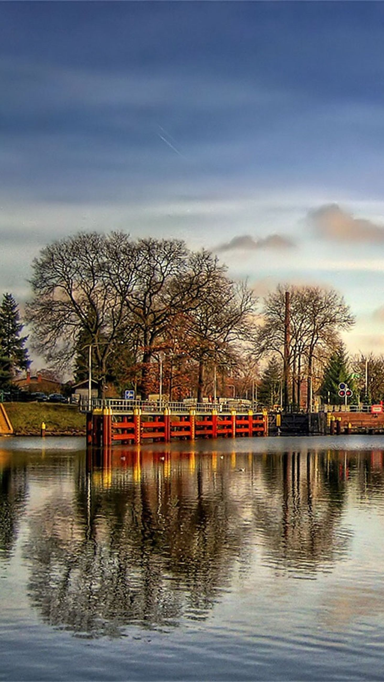 tree, bare tree, water, waterfront, sky, lake, river, built structure, reflection, architecture, cloud - sky, tranquility, building exterior, nature, tranquil scene, cloud, bridge - man made structure, rippled, outdoors, branch