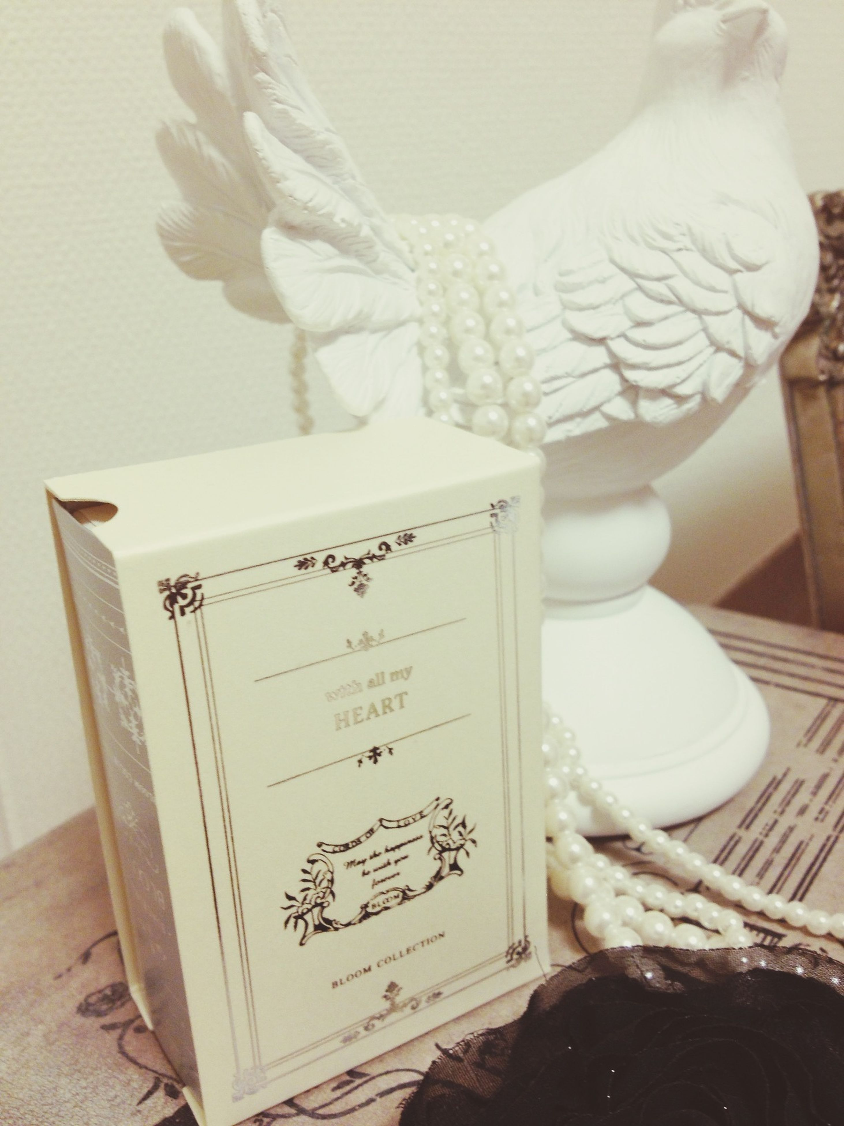 indoors, text, western script, communication, table, art and craft, art, creativity, book, human representation, paper, still life, close-up, home interior, animal representation, white color, non-western script, wall - building feature, wood - material, no people