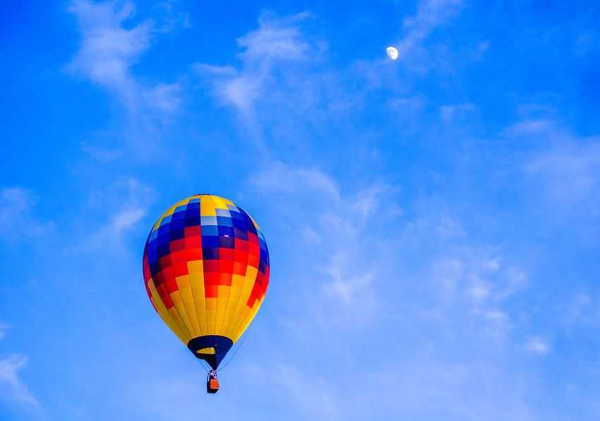 This colorful hot air balloon looks like its trying to fly to the moon Fun Hot Air Balloons Moon Adventure Air Vehicle Ballooning Festival Beauty In Nature Blue Blue Sky Cloud - Sky Day Extreme Sports Flying Hot Air Balloon Low Angle View Mid-air Multi Colored Nature Outdoors Sky Sport Transportation