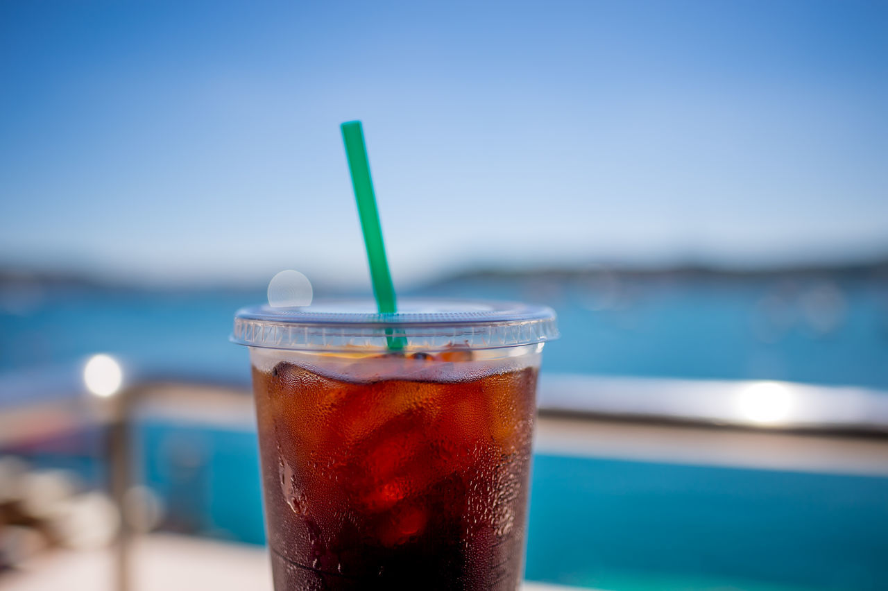 Close-Up Of Drink In Disposable Glass Against Sea