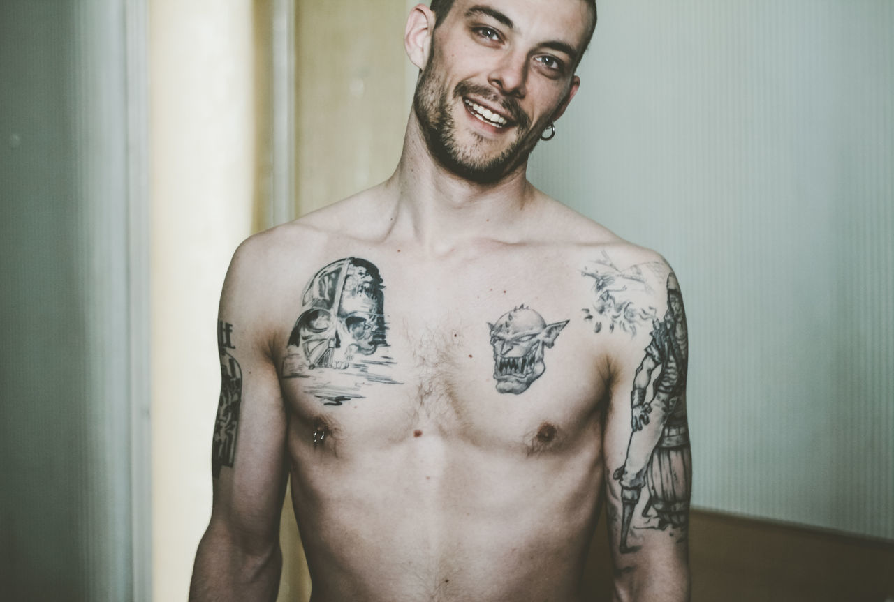 Portrait Of Shirtless Man With Tattoo Standing At Home