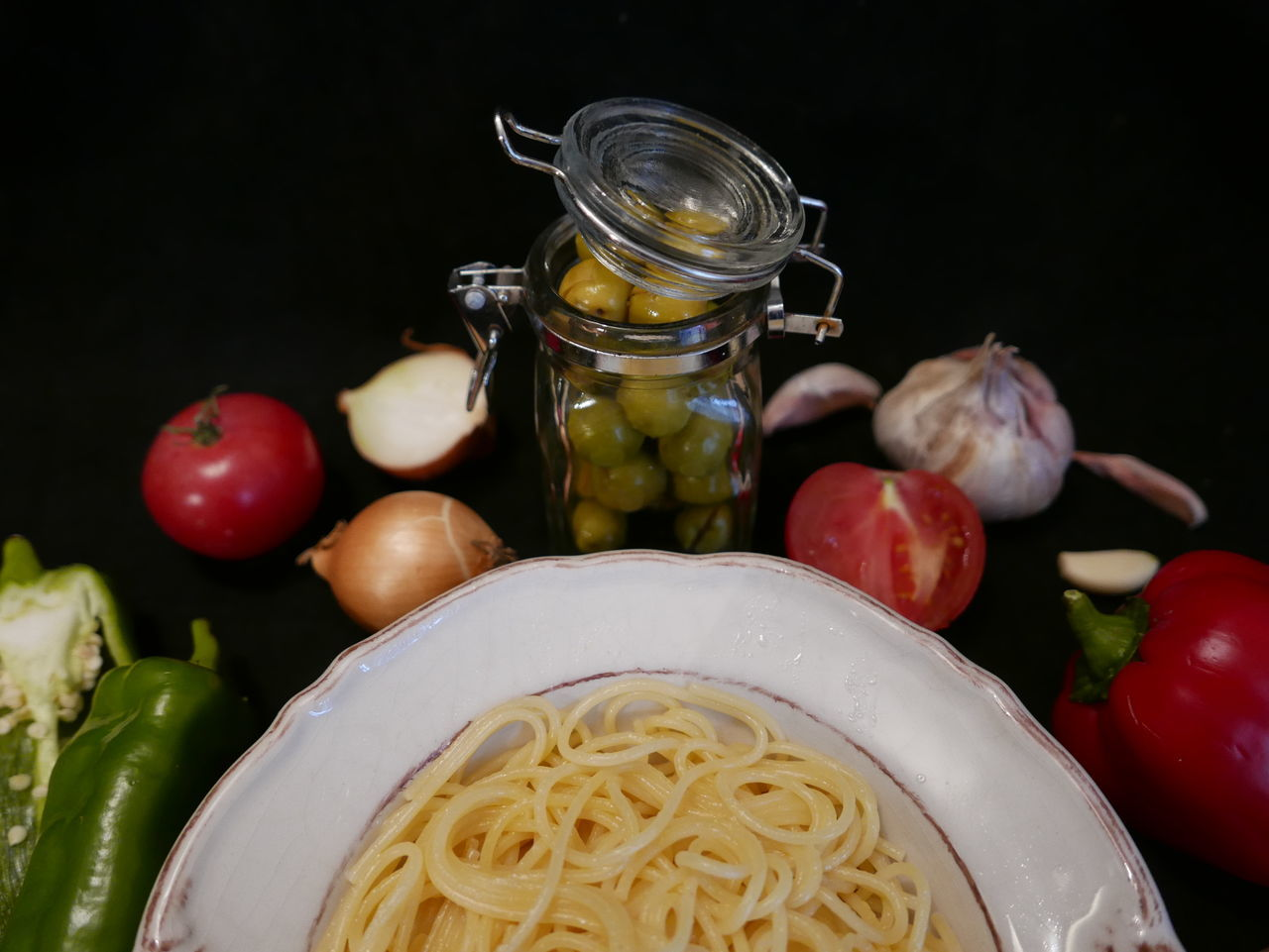 Close-Up Of Vegetables With Spaghetti Against Black Background