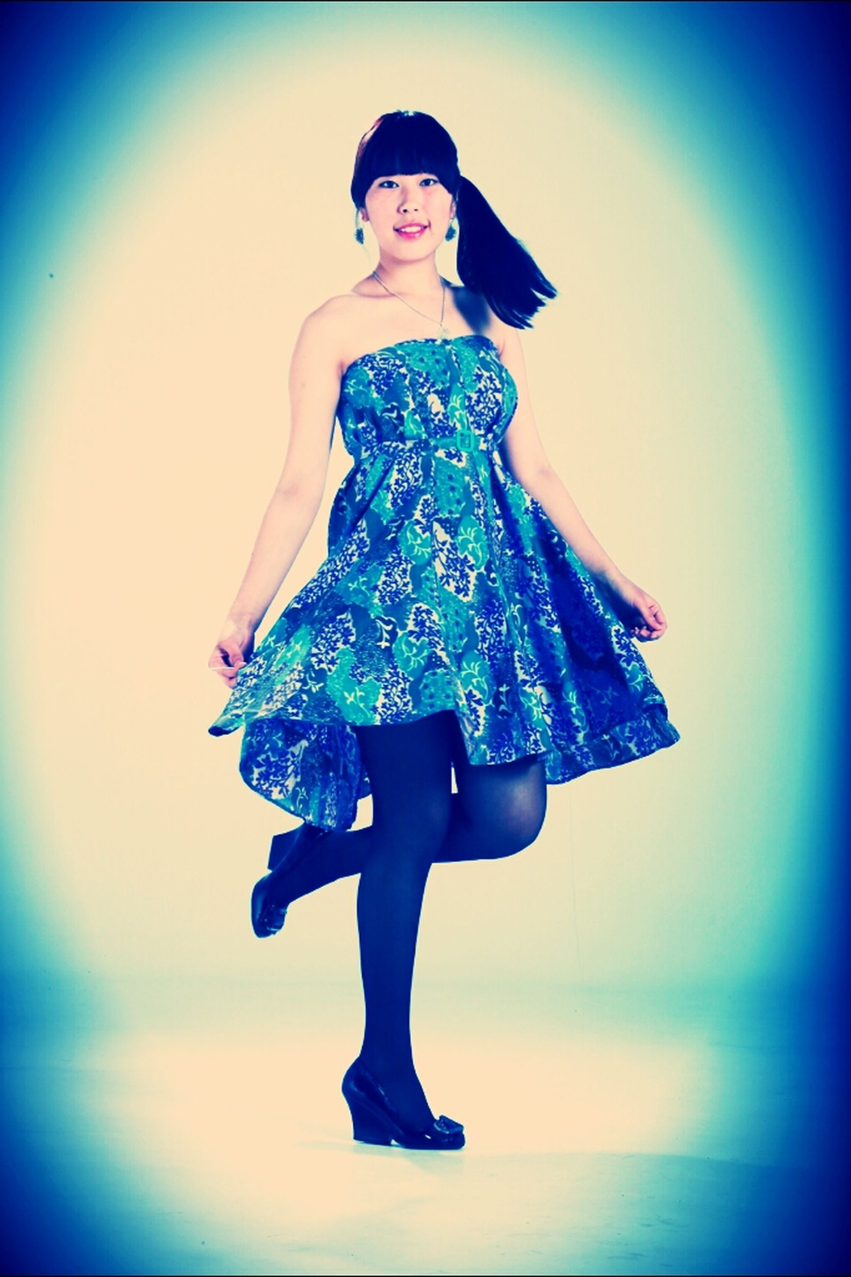 full length, lifestyles, front view, standing, leisure activity, arms outstretched, casual clothing, blue, young adult, person, looking at camera, portrait, young women, low angle view, arms raised, mid-air, dress, fun
