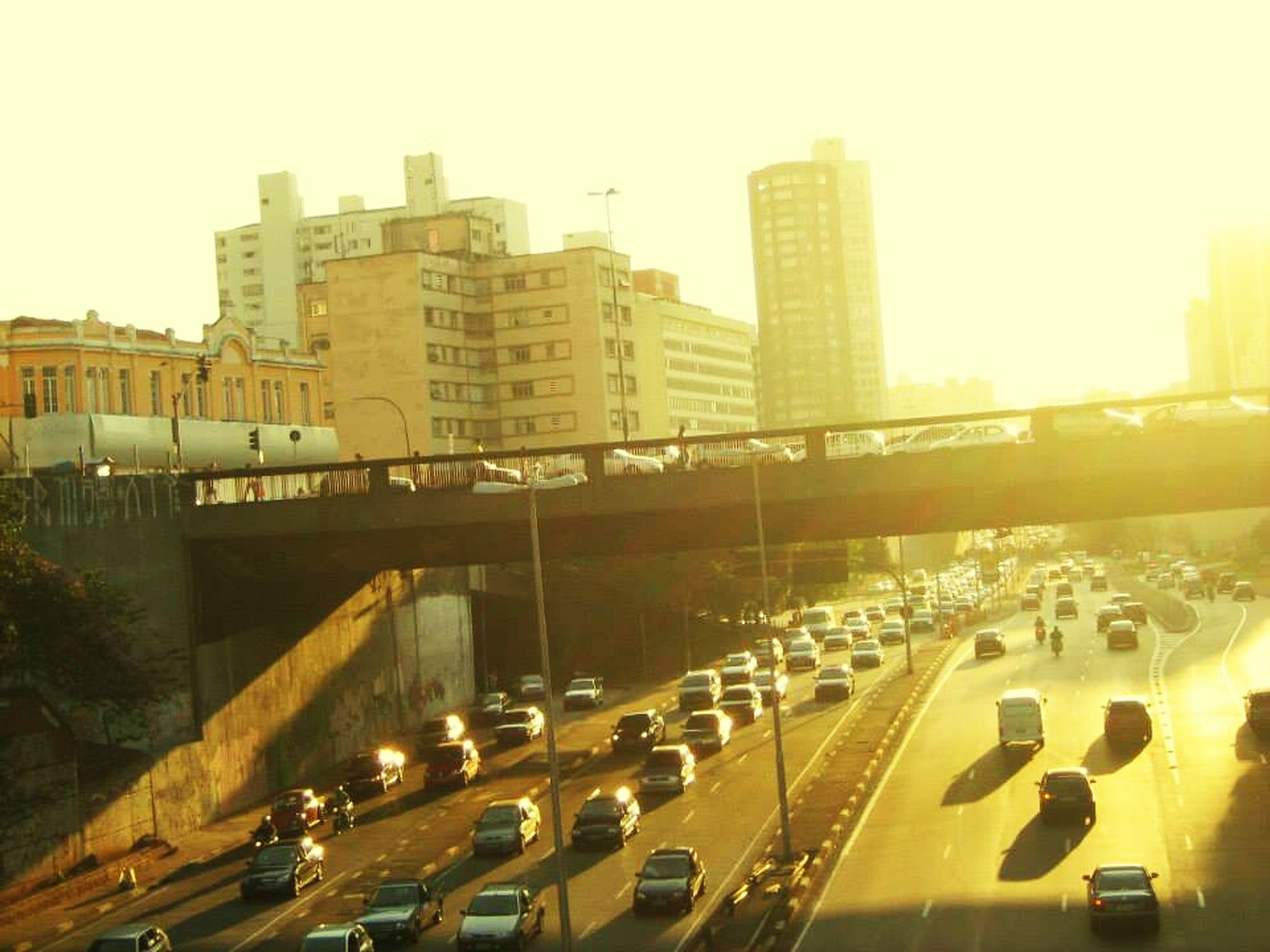 architecture, transportation, built structure, building exterior, city, car, land vehicle, mode of transport, high angle view, traffic, road, street, clear sky, city life, bridge - man made structure, city street, connection, public transportation, on the move, outdoors