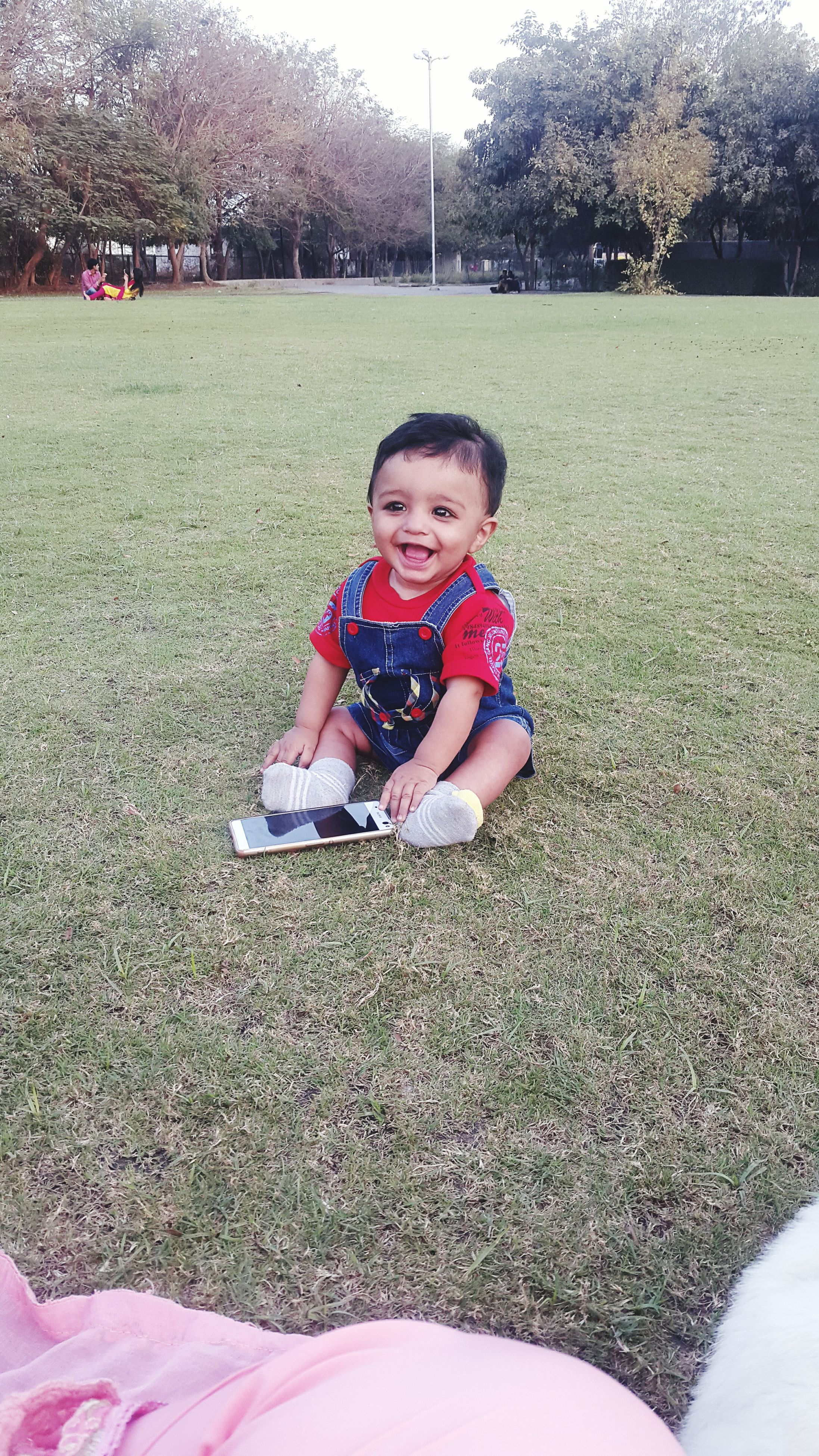 person, looking at camera, portrait, lifestyles, leisure activity, casual clothing, smiling, sitting, childhood, happiness, elementary age, park - man made space, full length, front view, cute, girls, grass, innocence