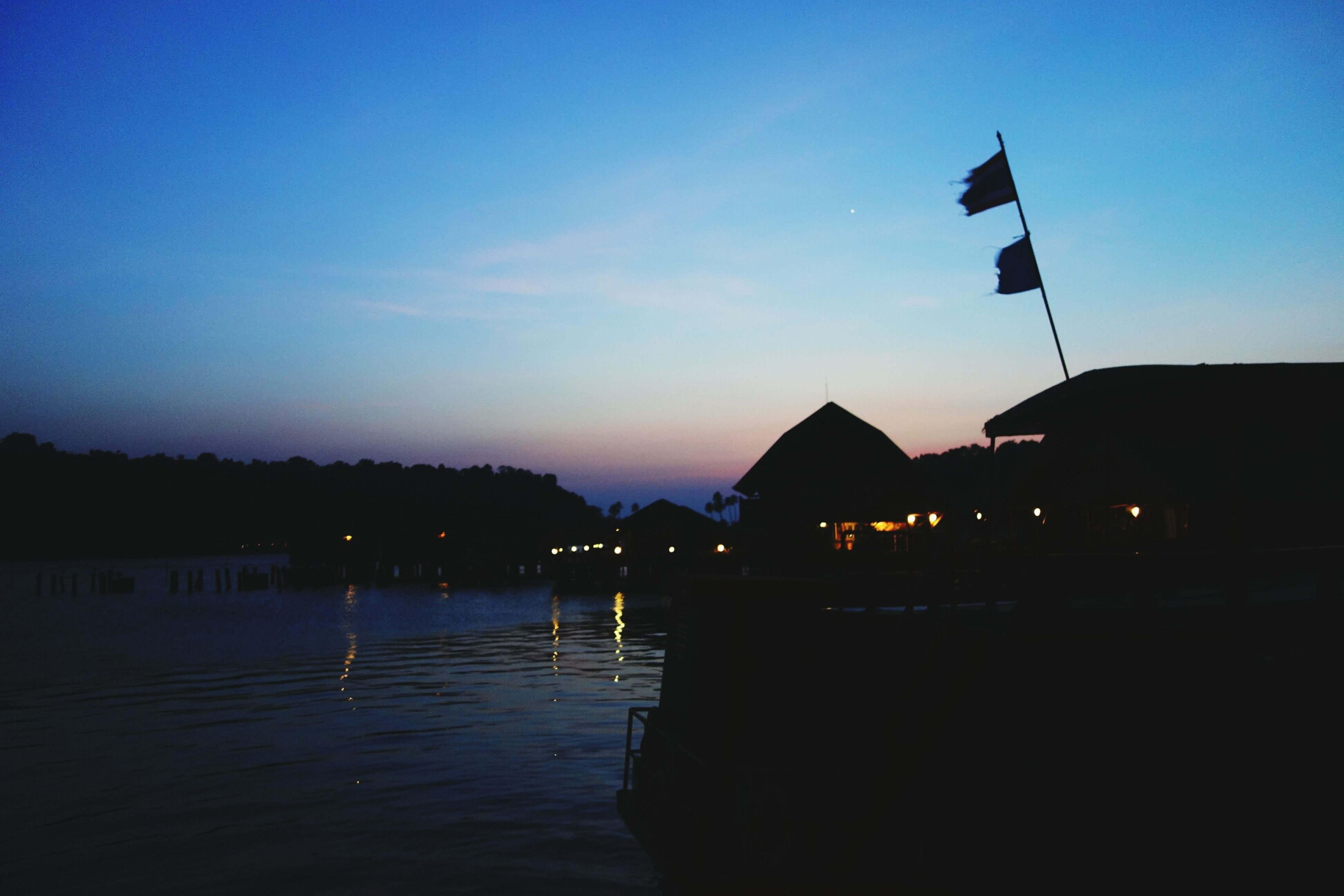 illuminated, silhouette, water, built structure, architecture, sunset, sky, dusk, building exterior, reflection, night, blue, tranquility, river, scenics, lighting equipment, nature, lake, waterfront, tranquil scene
