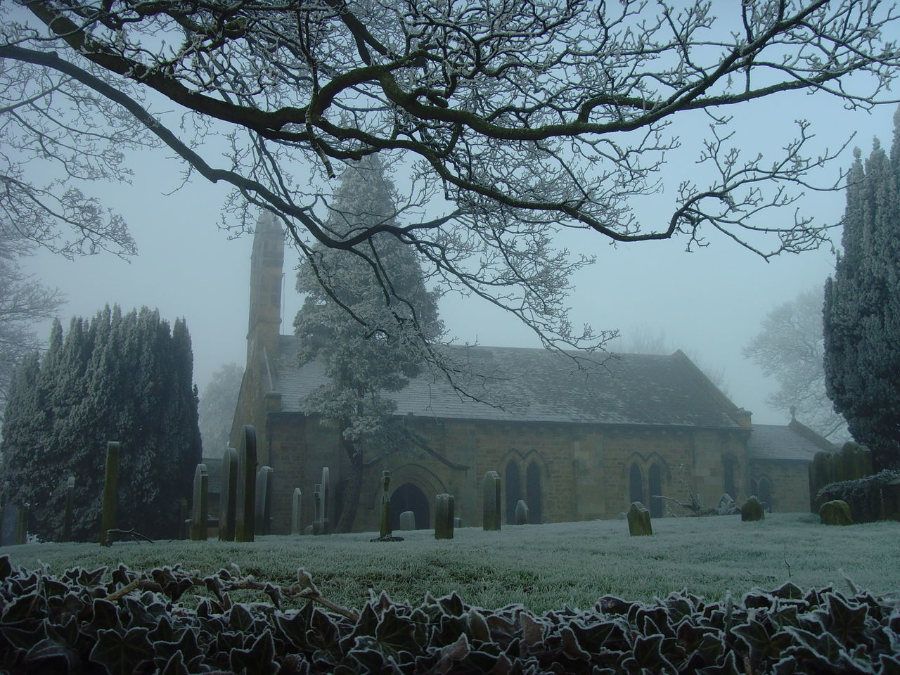 Church And Cemetery Against Sky In Foggy Weather