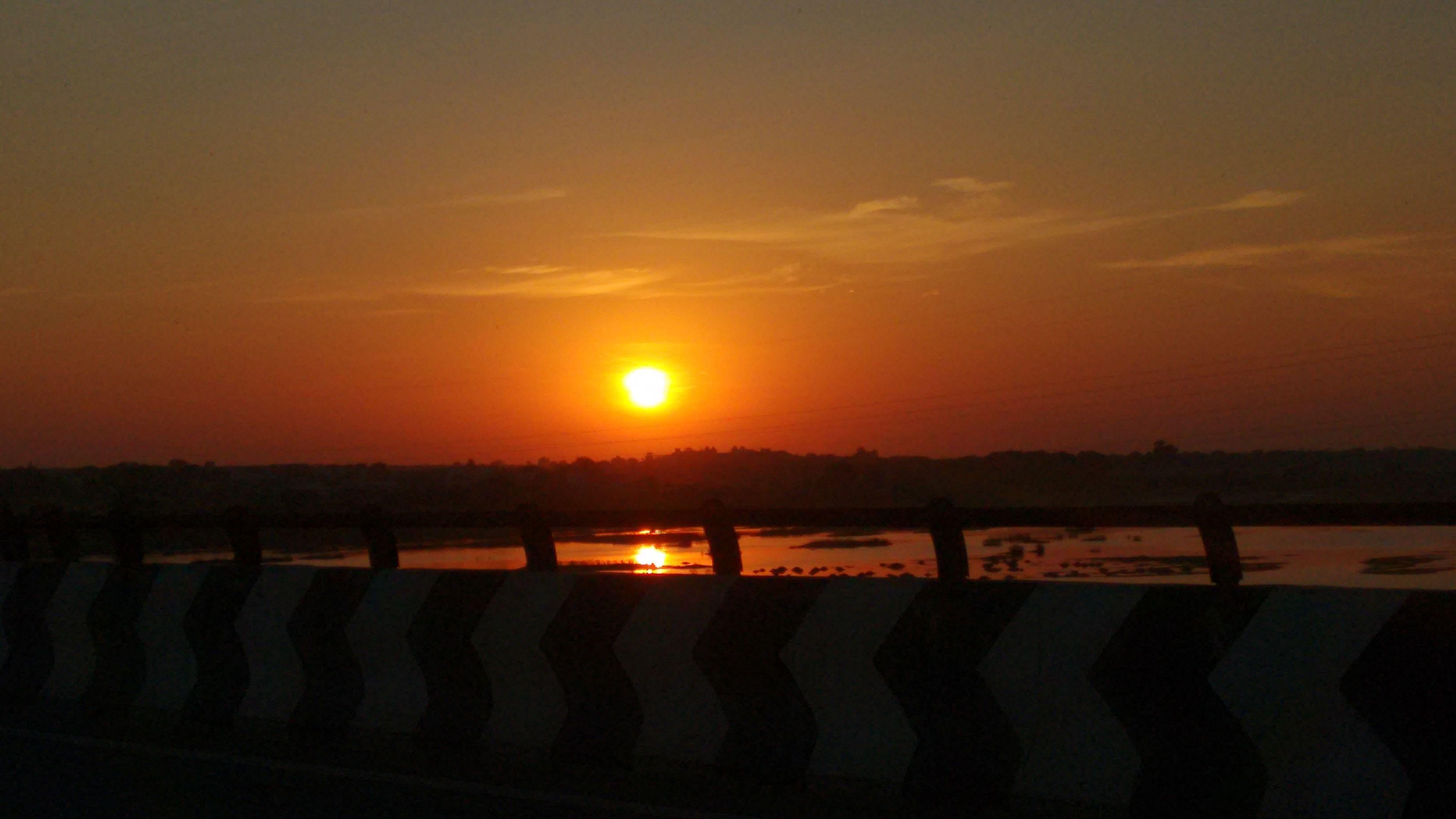 sunset, sun, orange color, silhouette, scenics, sky, tranquil scene, tranquility, beauty in nature, landscape, nature, idyllic, sunlight, cloud - sky, lens flare, field, no people, railing, outdoors, sunbeam