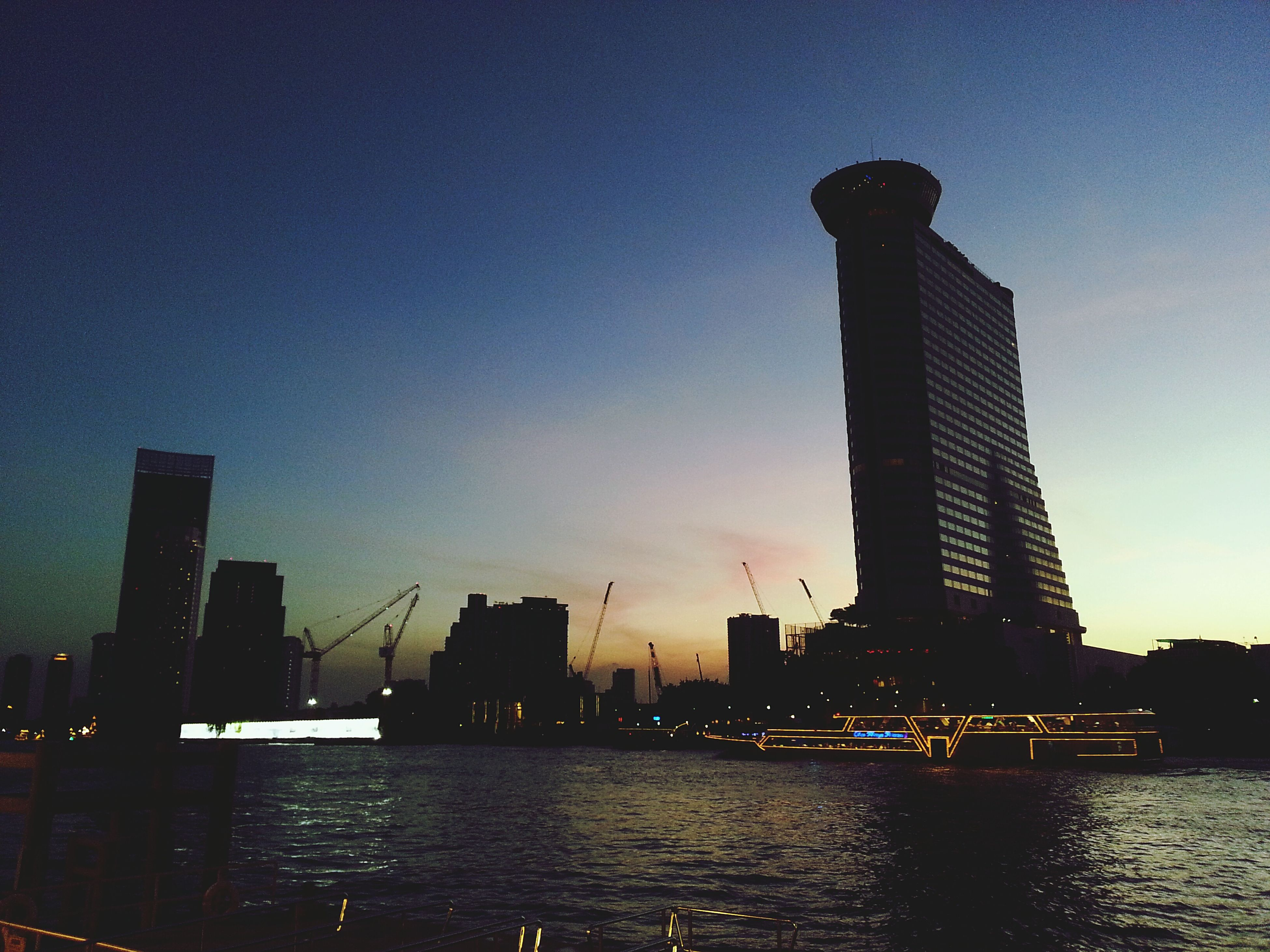 architecture, built structure, building exterior, city, water, waterfront, river, skyscraper, silhouette, sky, tall - high, sunset, tower, urban skyline, dusk, crane - construction machinery, low angle view, modern, cityscape, reflection