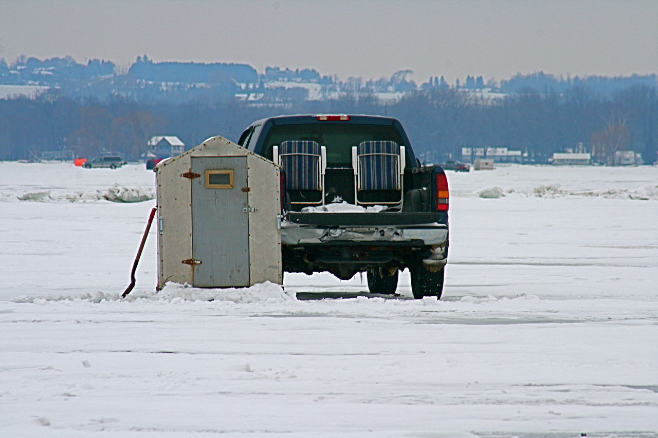 Ice fishing and a truck Cold Cold Temperature Ice Fishing Huts Land Vehicle Outdoors Recreational Pursuit Small Ice Fishing Hut Snow Transportation Winter