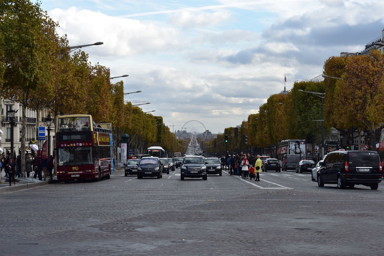Standing under the Arc de Triomphe looking at the champs elysees Cars Ferrys Wheel Arc De Triomphe Architecture Building Exterior Bus Car Champs Elysees City Cloud - Sky Day Land Vehicle Mode Of Transport Outdoors Real People Road Sky Street Street Art Street Photography Streetphotography Transportation