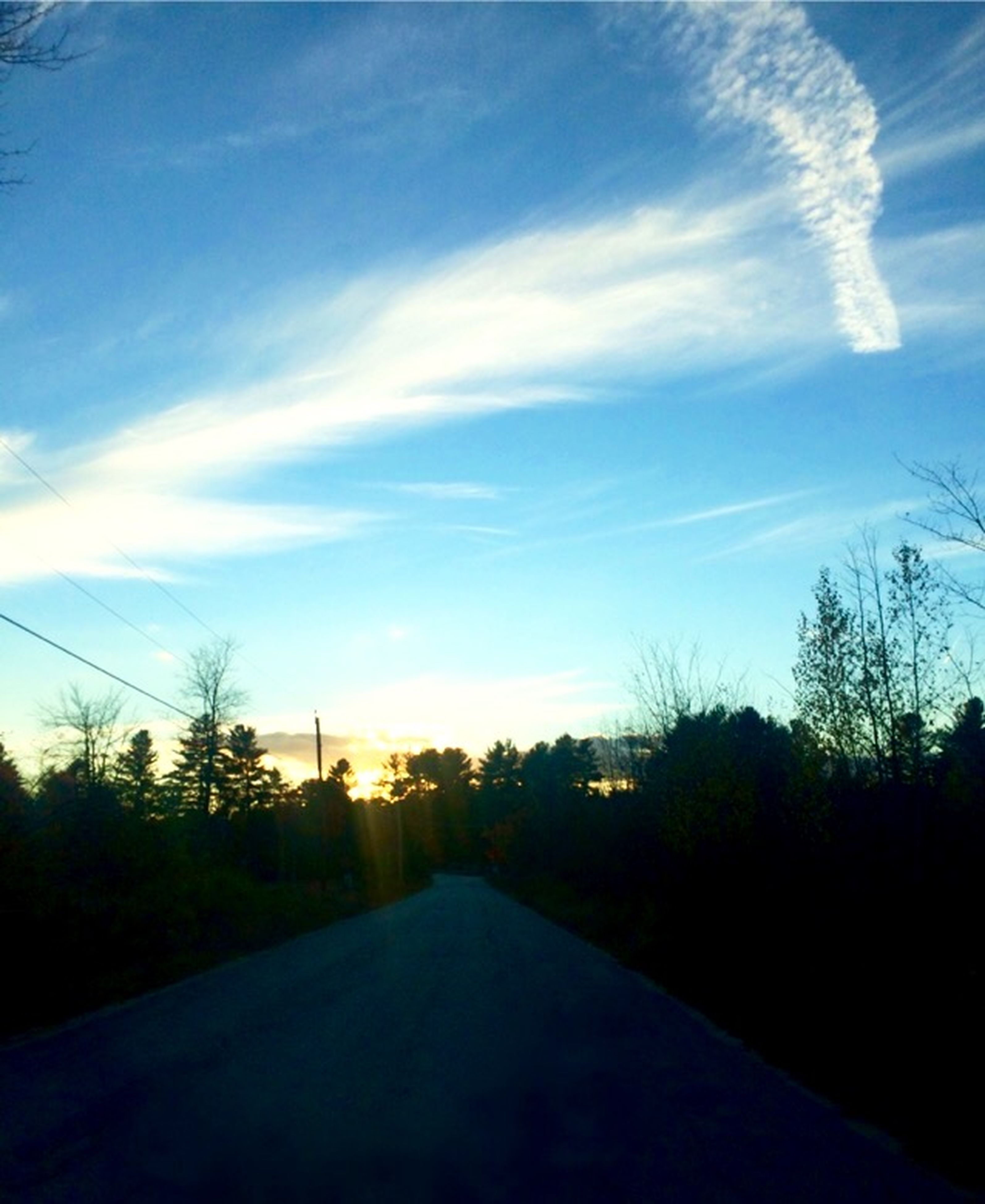 sky, the way forward, tree, road, sunset, diminishing perspective, silhouette, electricity pylon, tranquility, cloud - sky, power line, cloud, tranquil scene, blue, transportation, vanishing point, nature, long, no people, outdoors