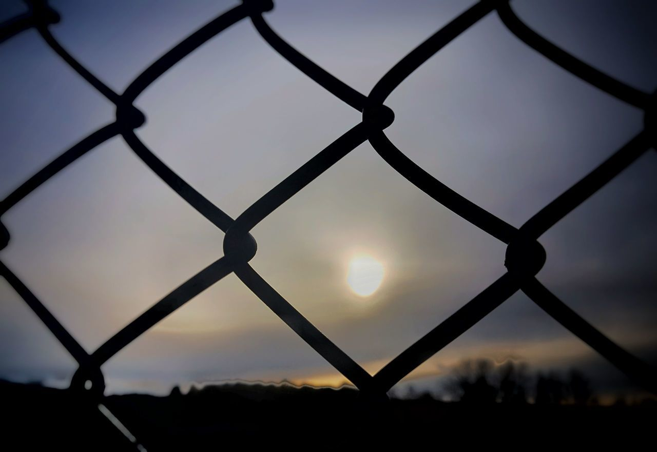 sunset, chainlink fence, sky, sun, silhouette, focus on foreground, nature, no people, outdoors, close-up, beauty in nature, day